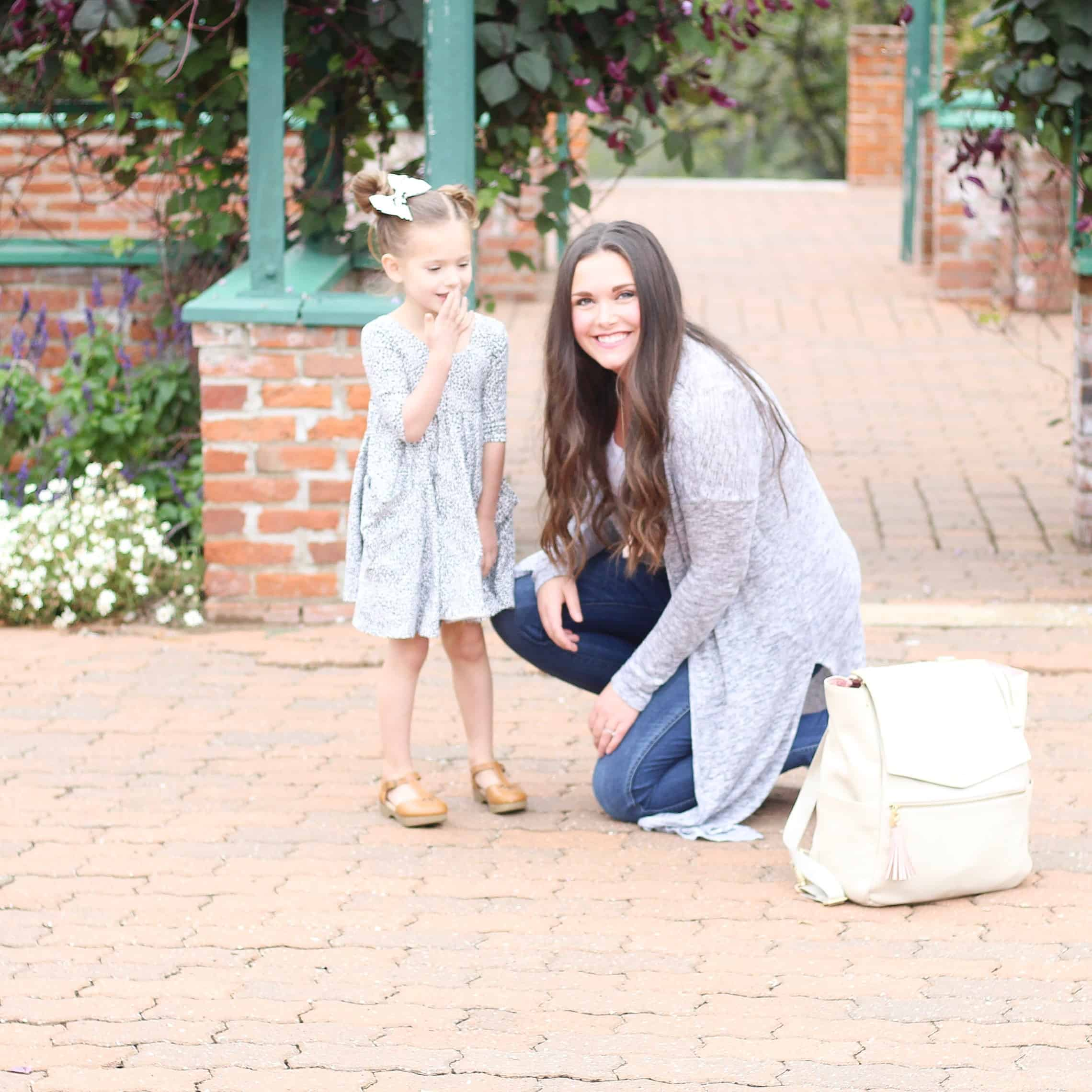 mom and daughter on red brick next to Freshly Picked Diaper bag