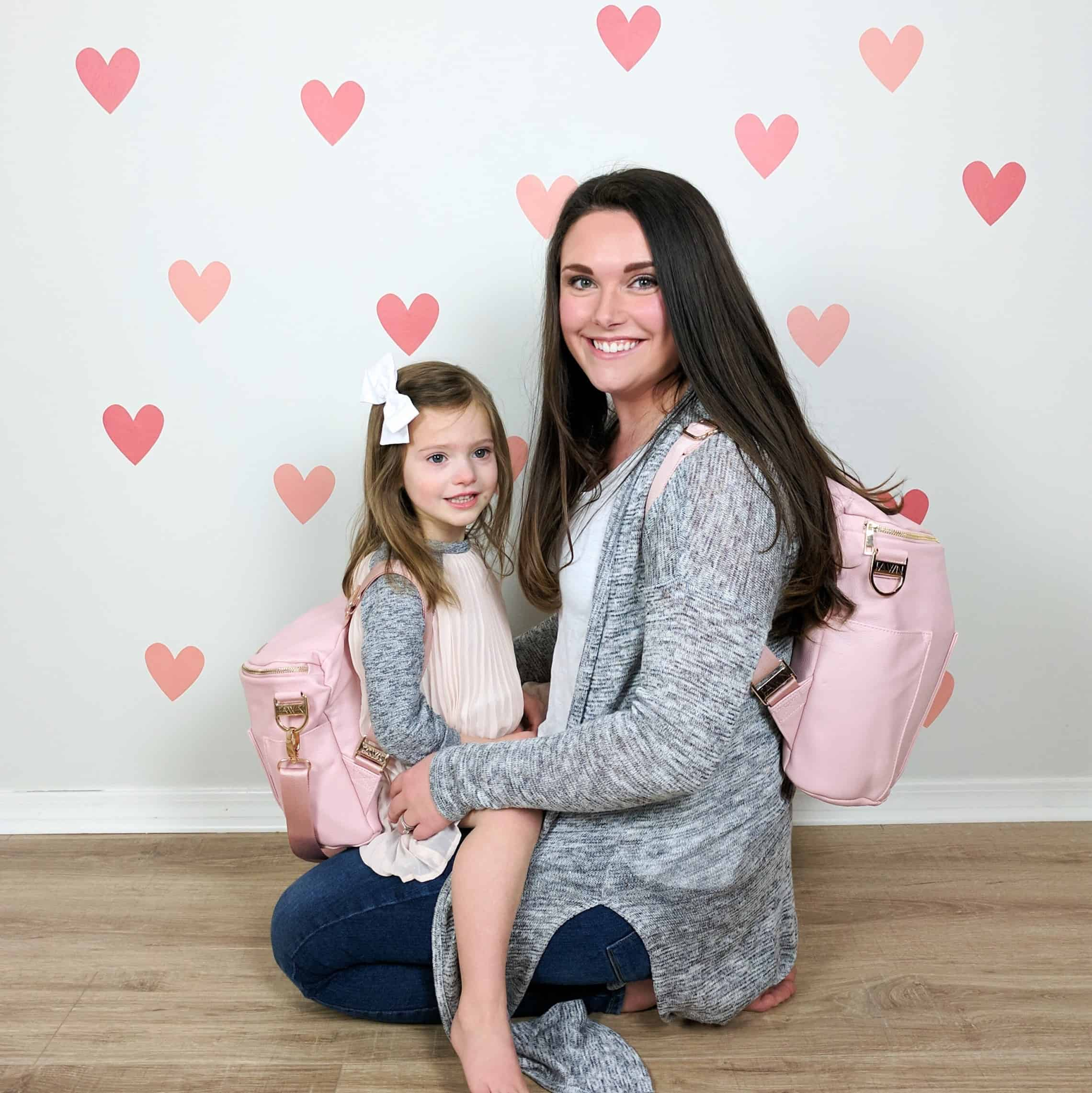 mom and daughter in matching fawn design diaper bags against pink heart wall