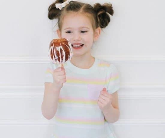 Little girl eating a unicorn caramel apple