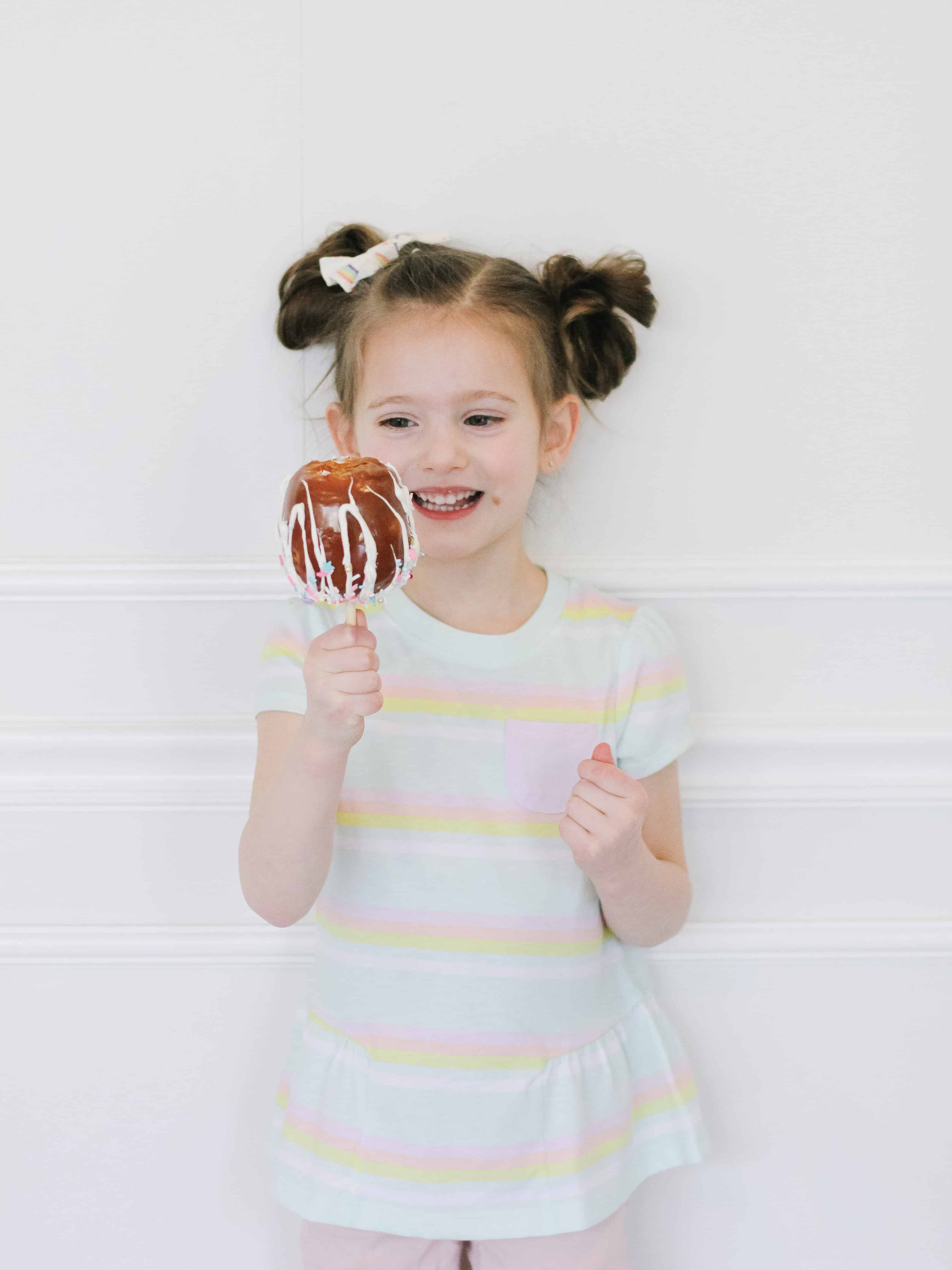 Little girl eating a unicorn caramel apple