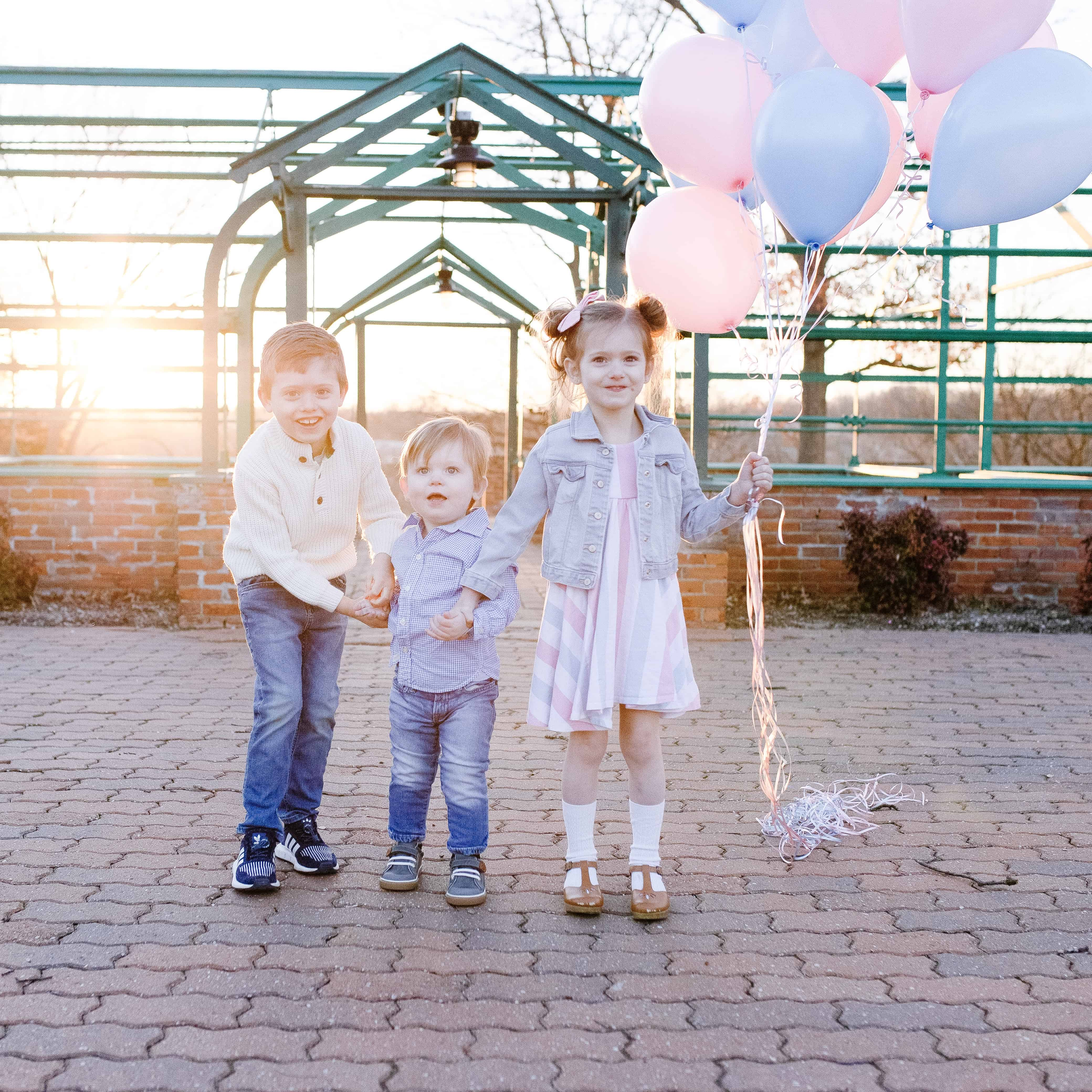 three kids with pink and blue balloons