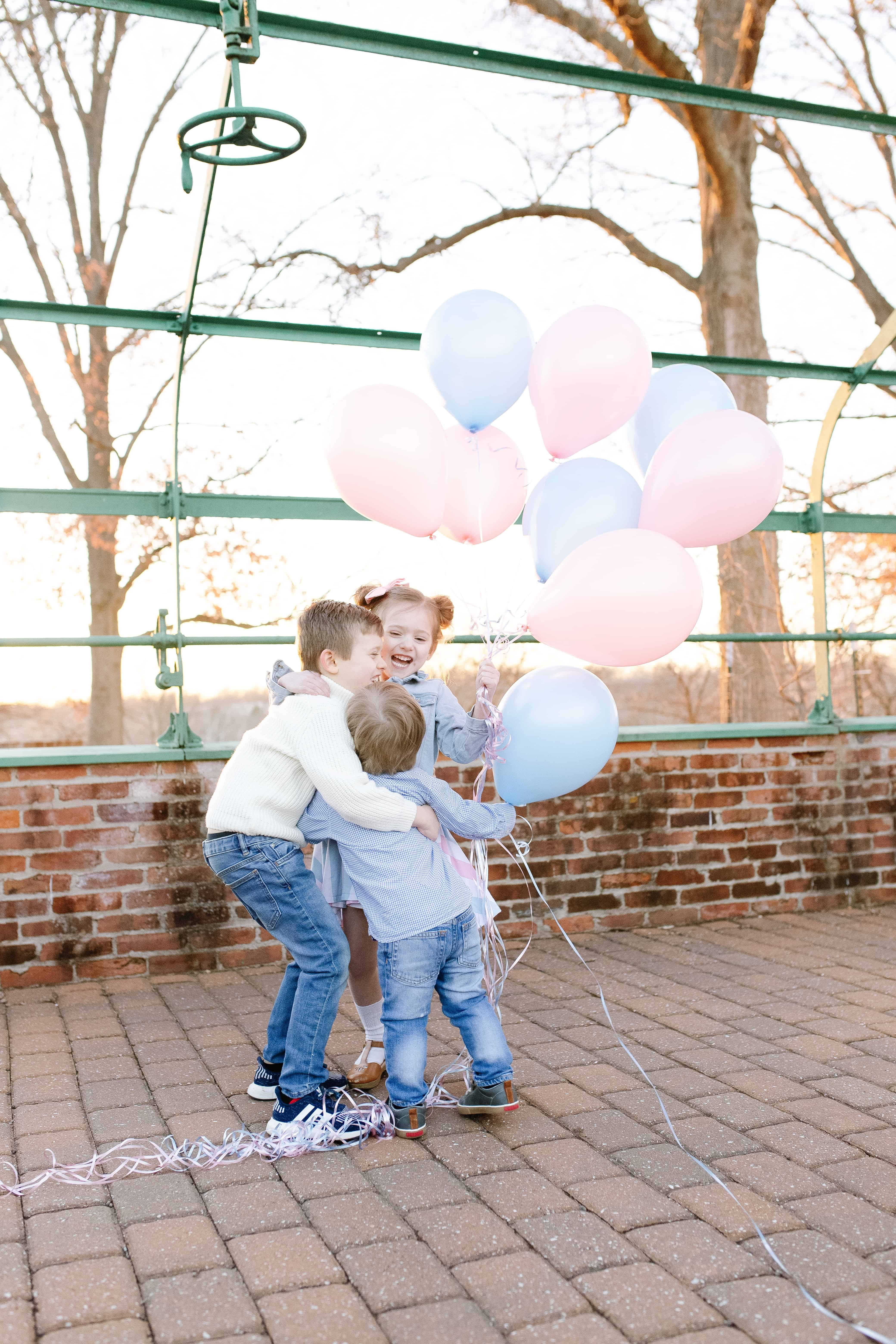 Siblings hugging with pink and blue balloons