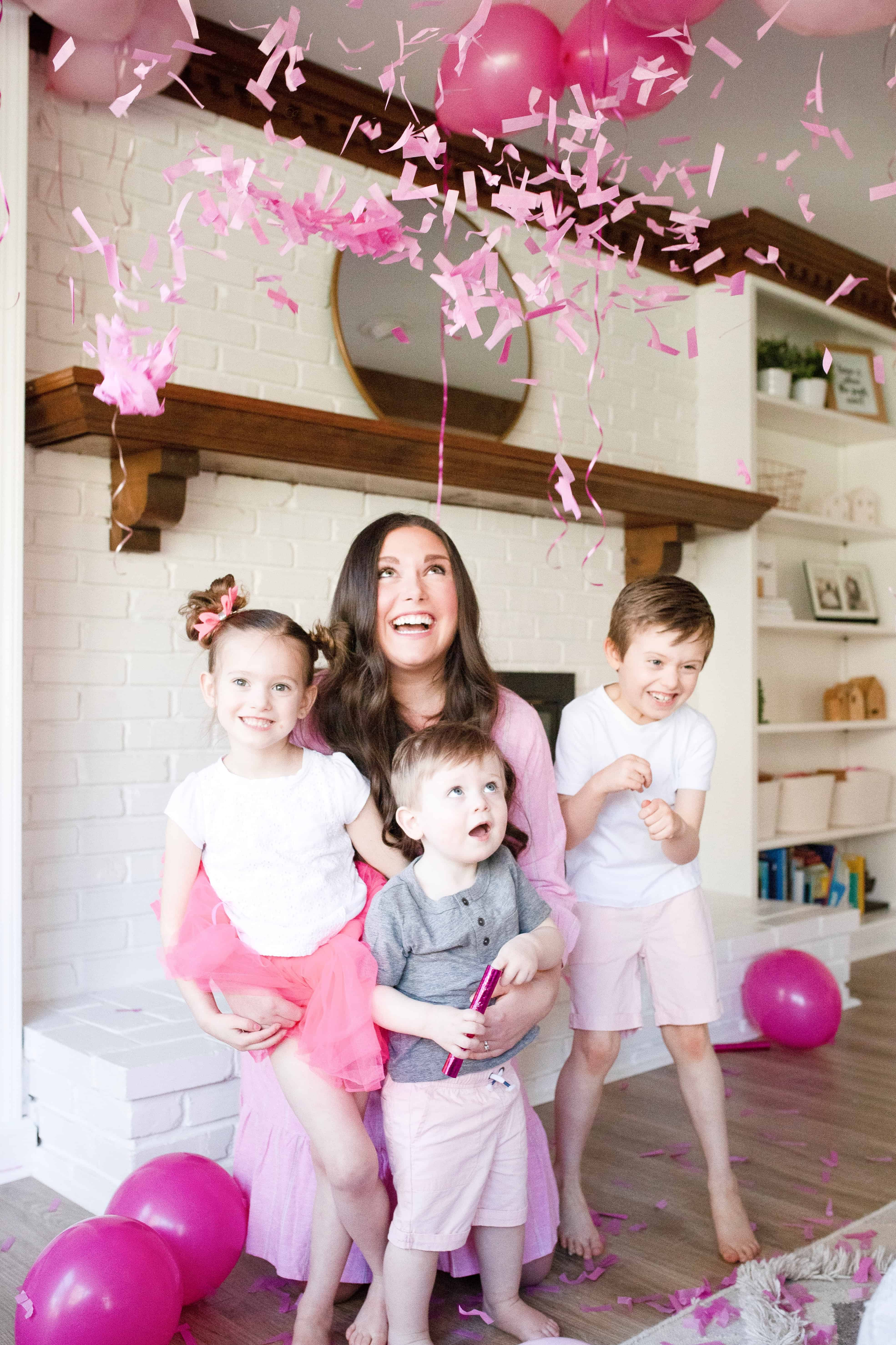 Mom with 3 kids in pink surrounded by pink confetti and balloons