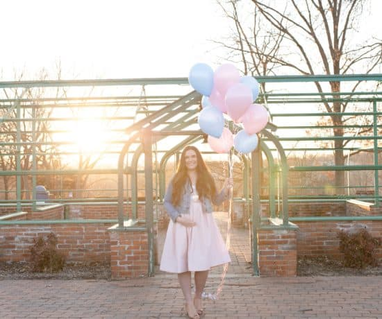 pregnant mom holding pink and blue balloons