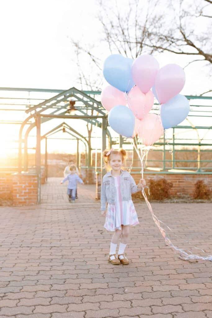 Little girl holding balloons waiting on gender reveal for from sneak peek gender test