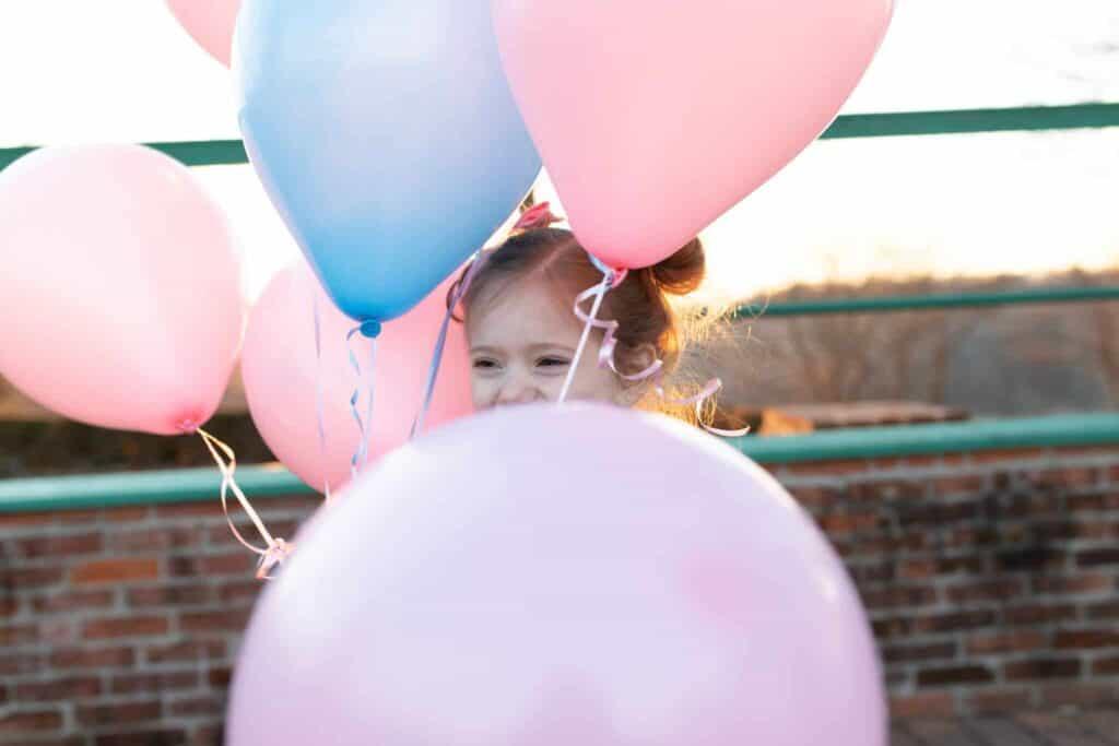 little girl hiding in balloons waiting for sneak peek test gender reveal