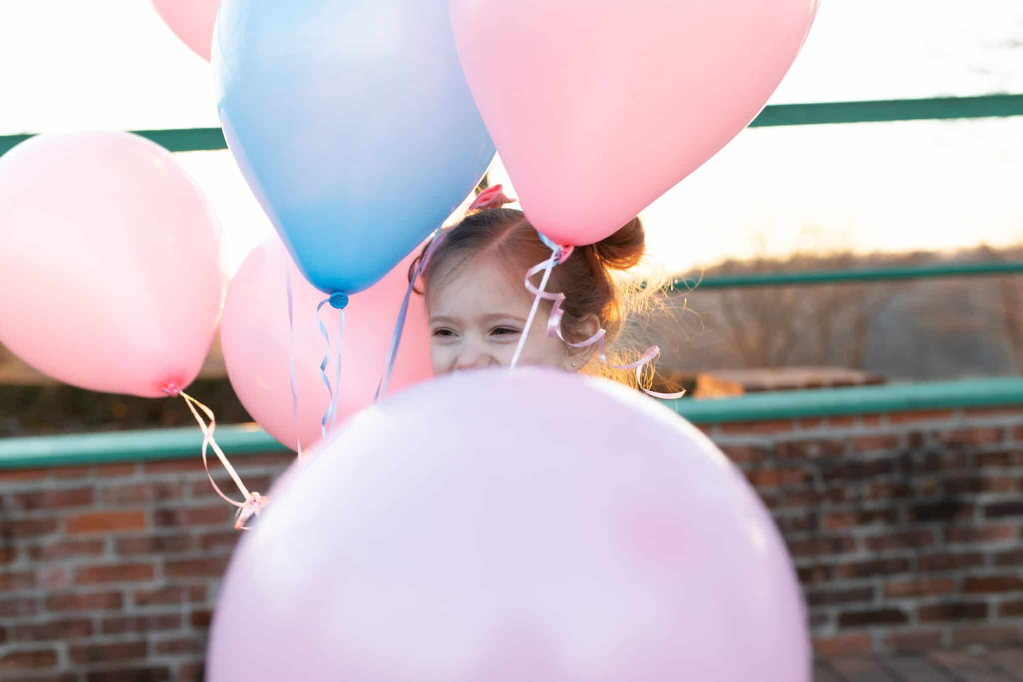 toddler girl with pink and blue balloons