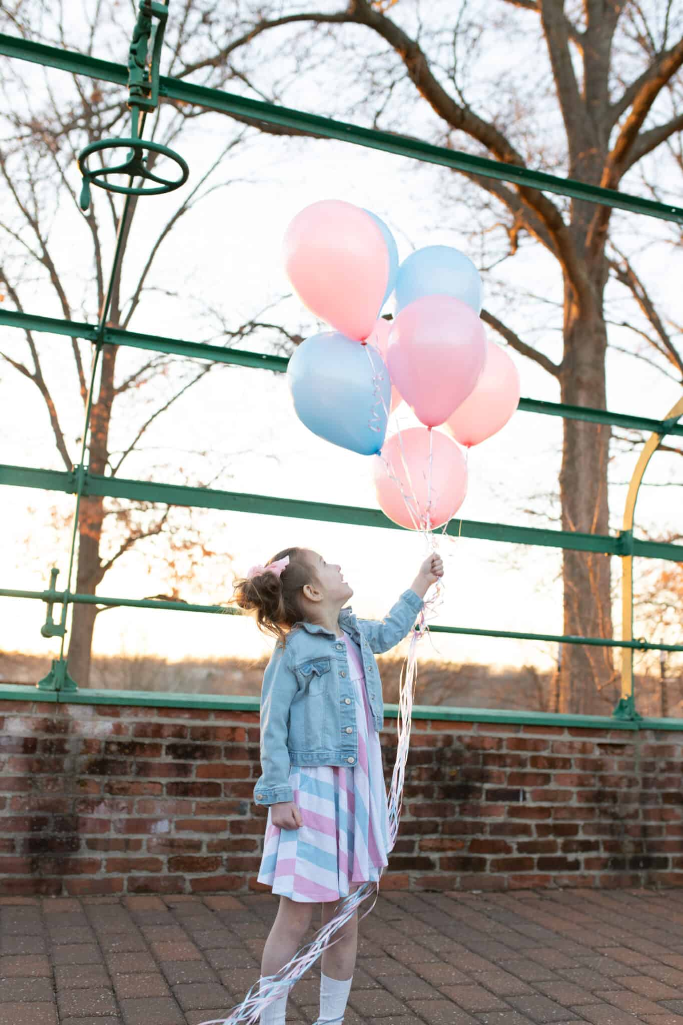 Toddler girl with pink and blue gender balloons