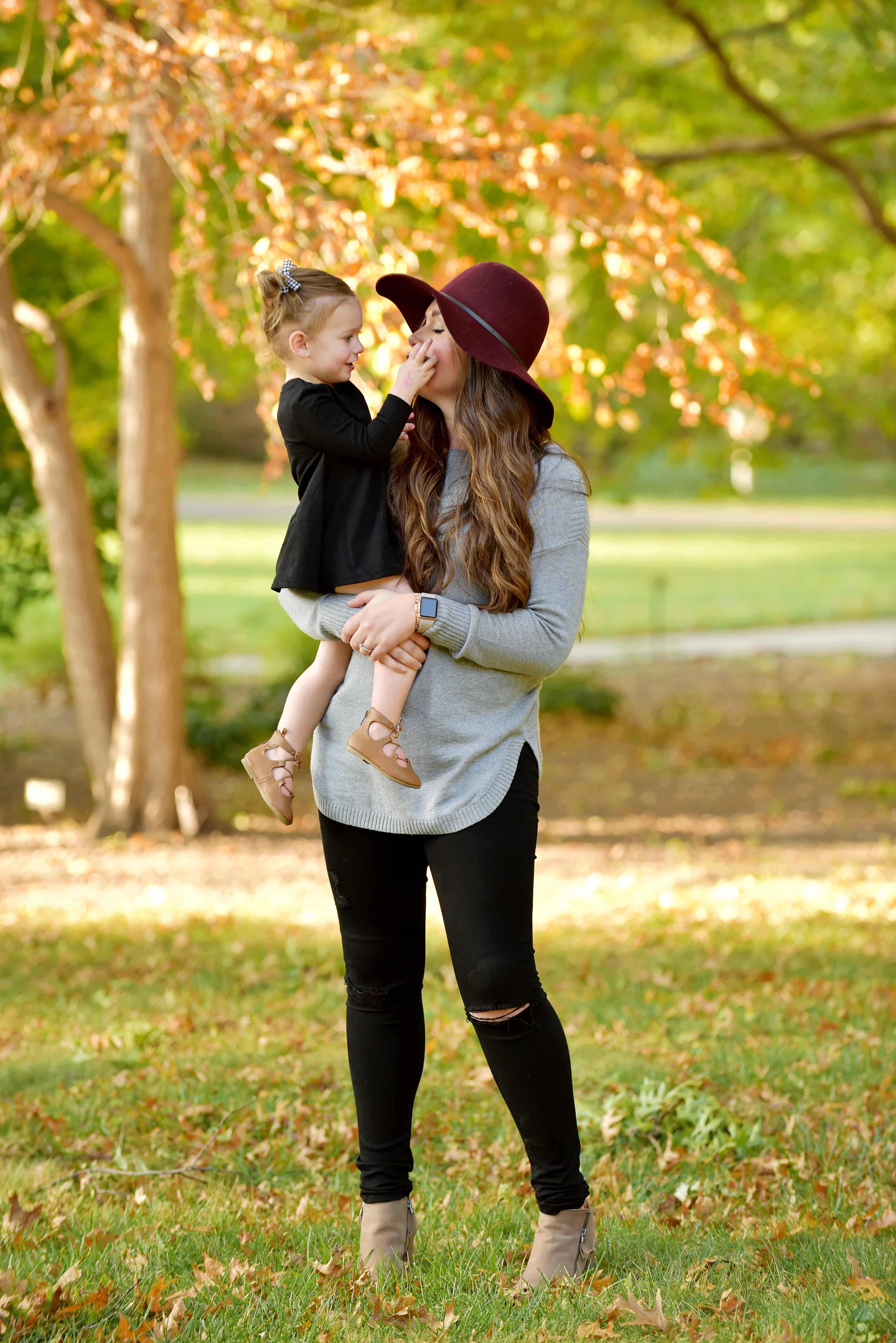 mom holding toddler girl wearing maroon hat