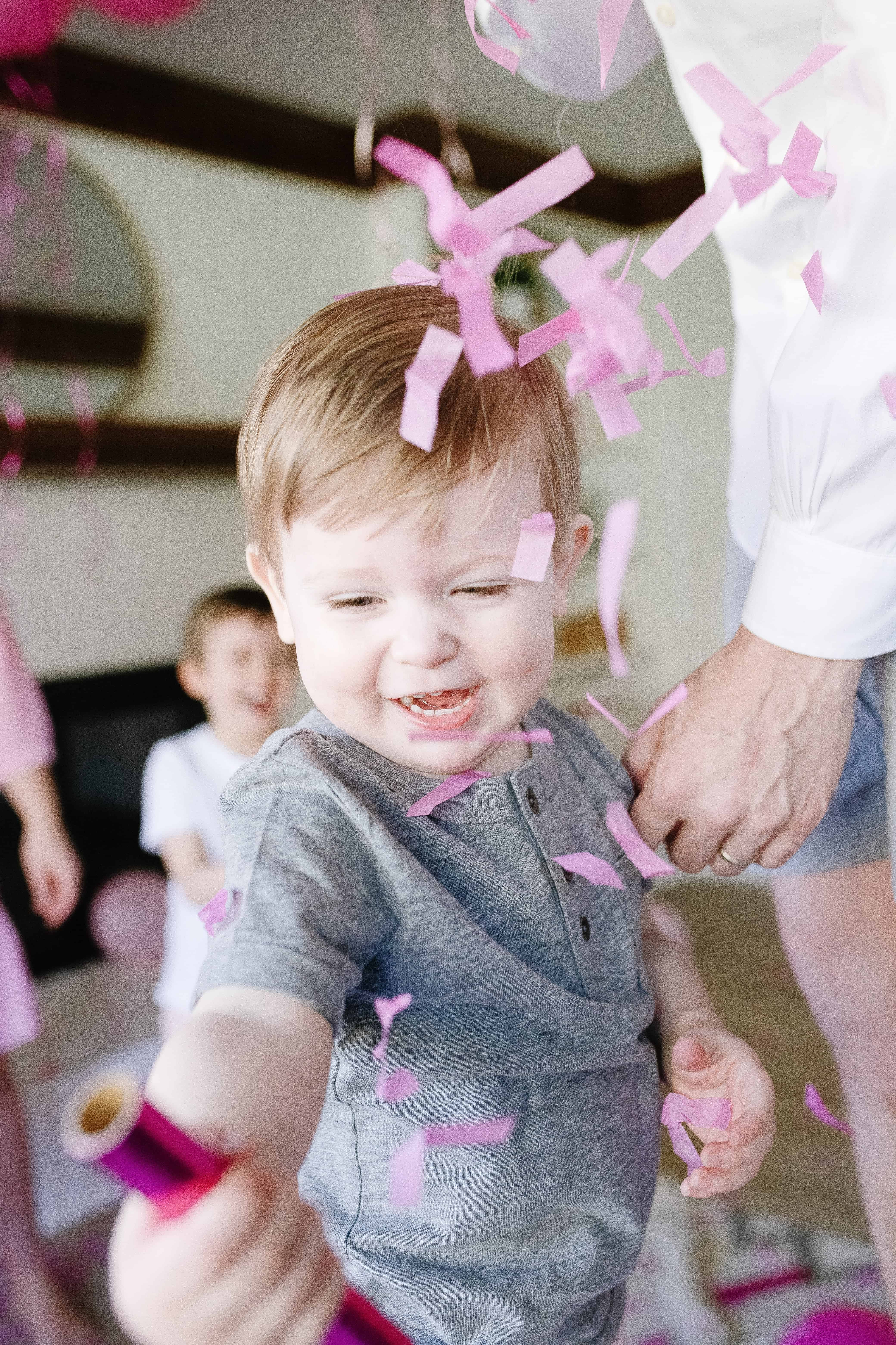toddler boy and pink confetti at gender reveal