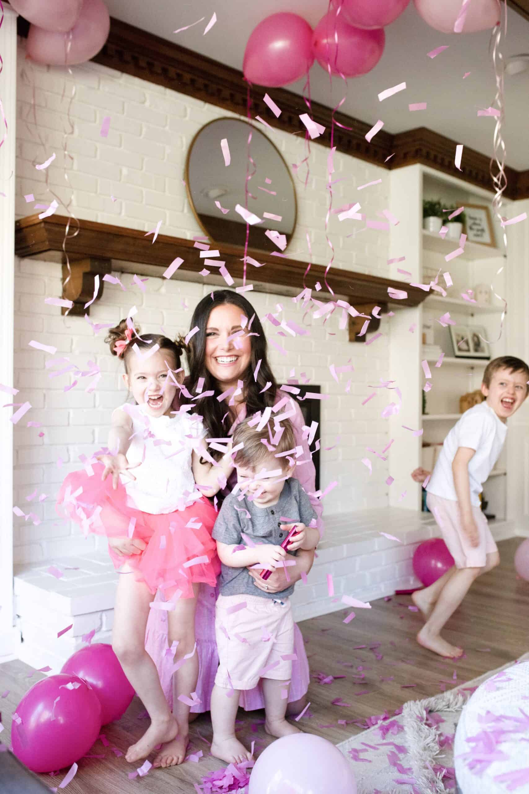 mom and 3 kids with pink confetti gender announcement