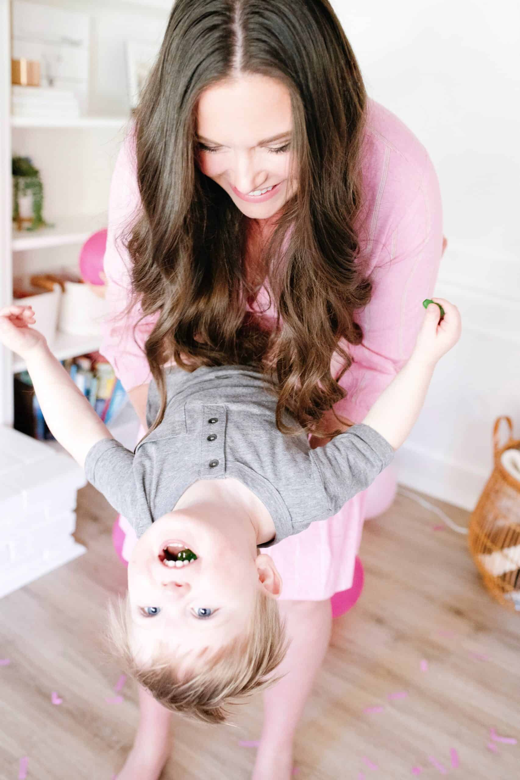 mom holding toddler boy upside down