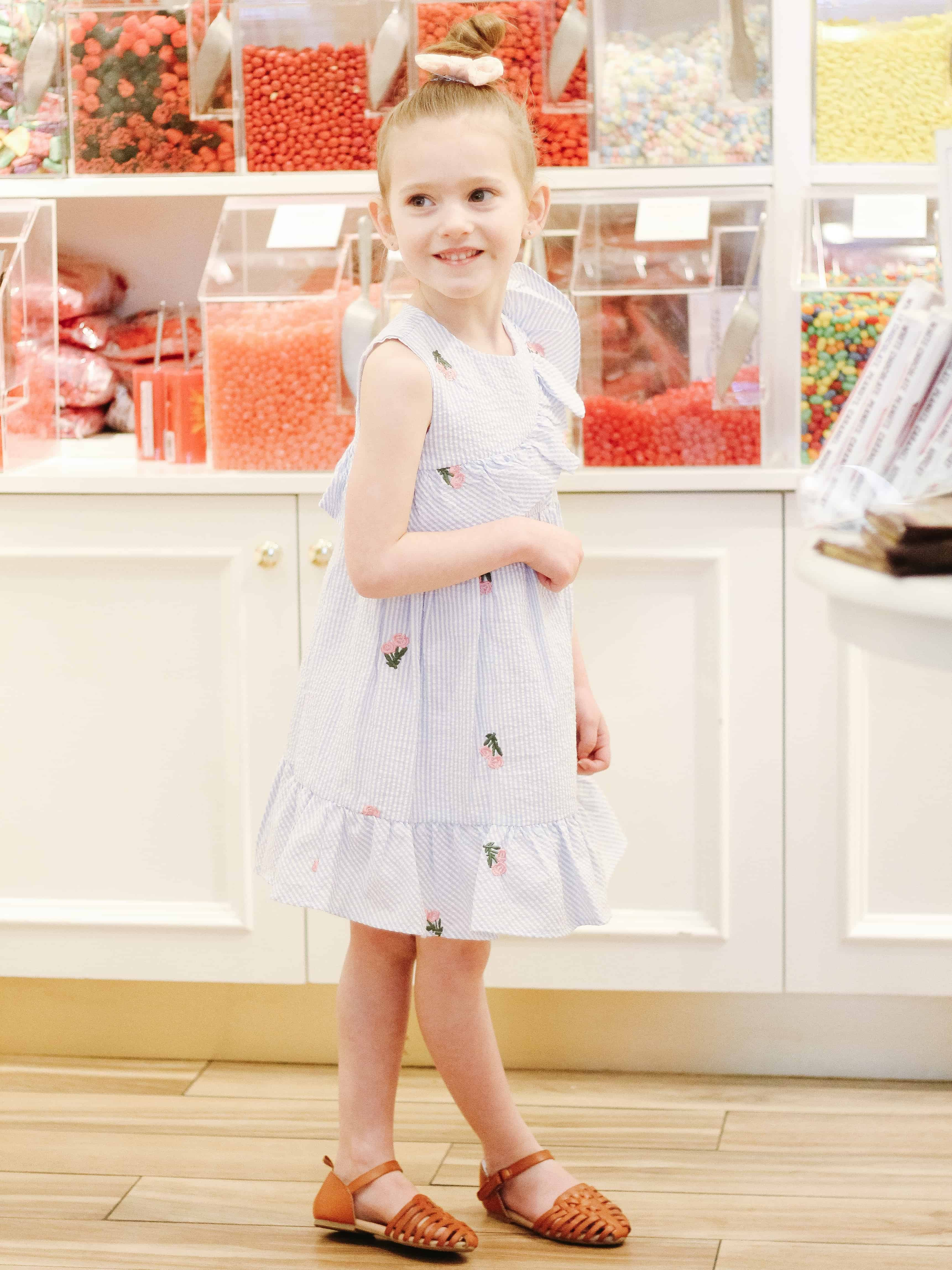 Toddler in blue seersucker dress at candy store