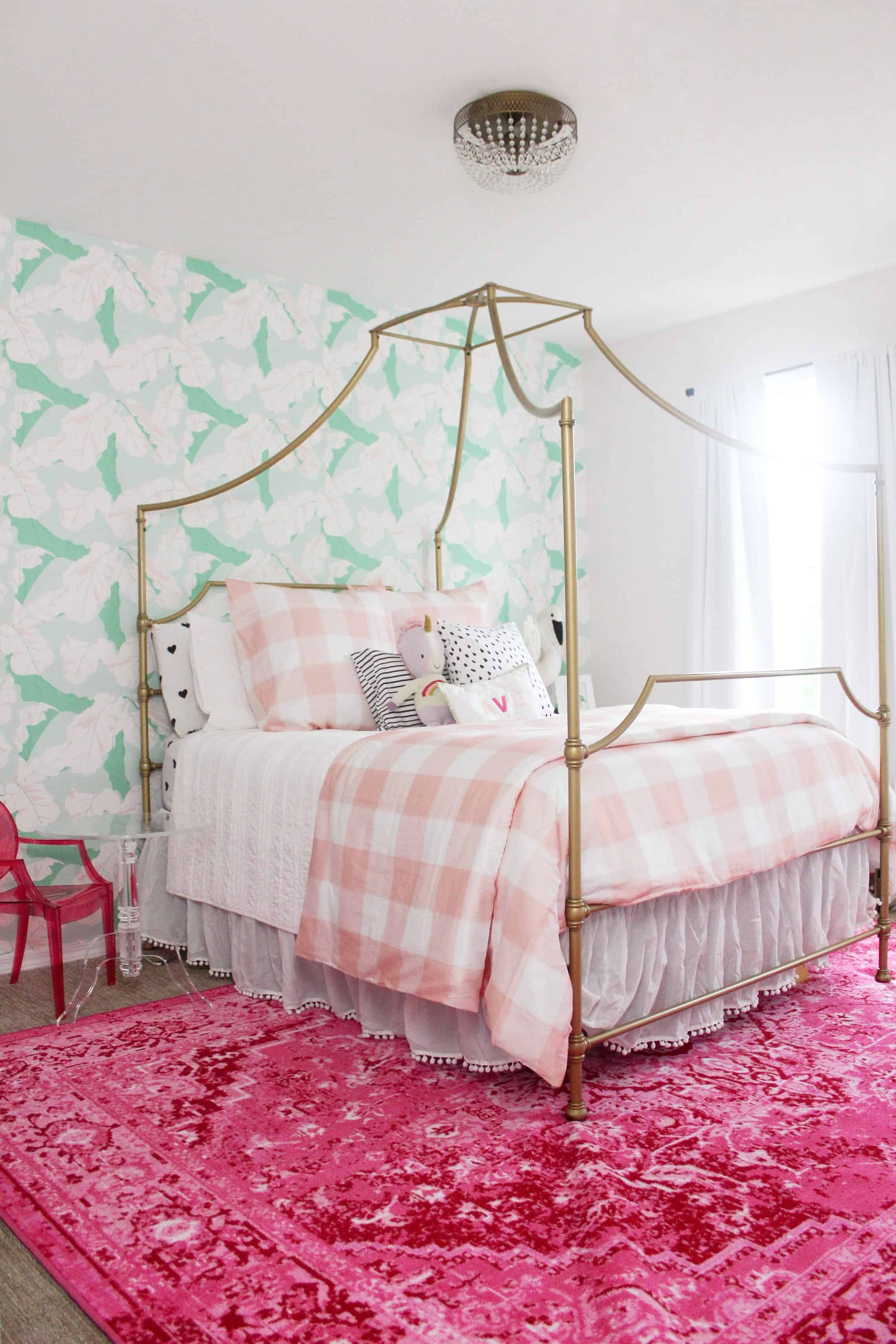 toddler girl room with pink and green wallpaper, pink rug, gold bed and pink gingham bedding  - tips for hanging Spoonflower water activated wallpaper