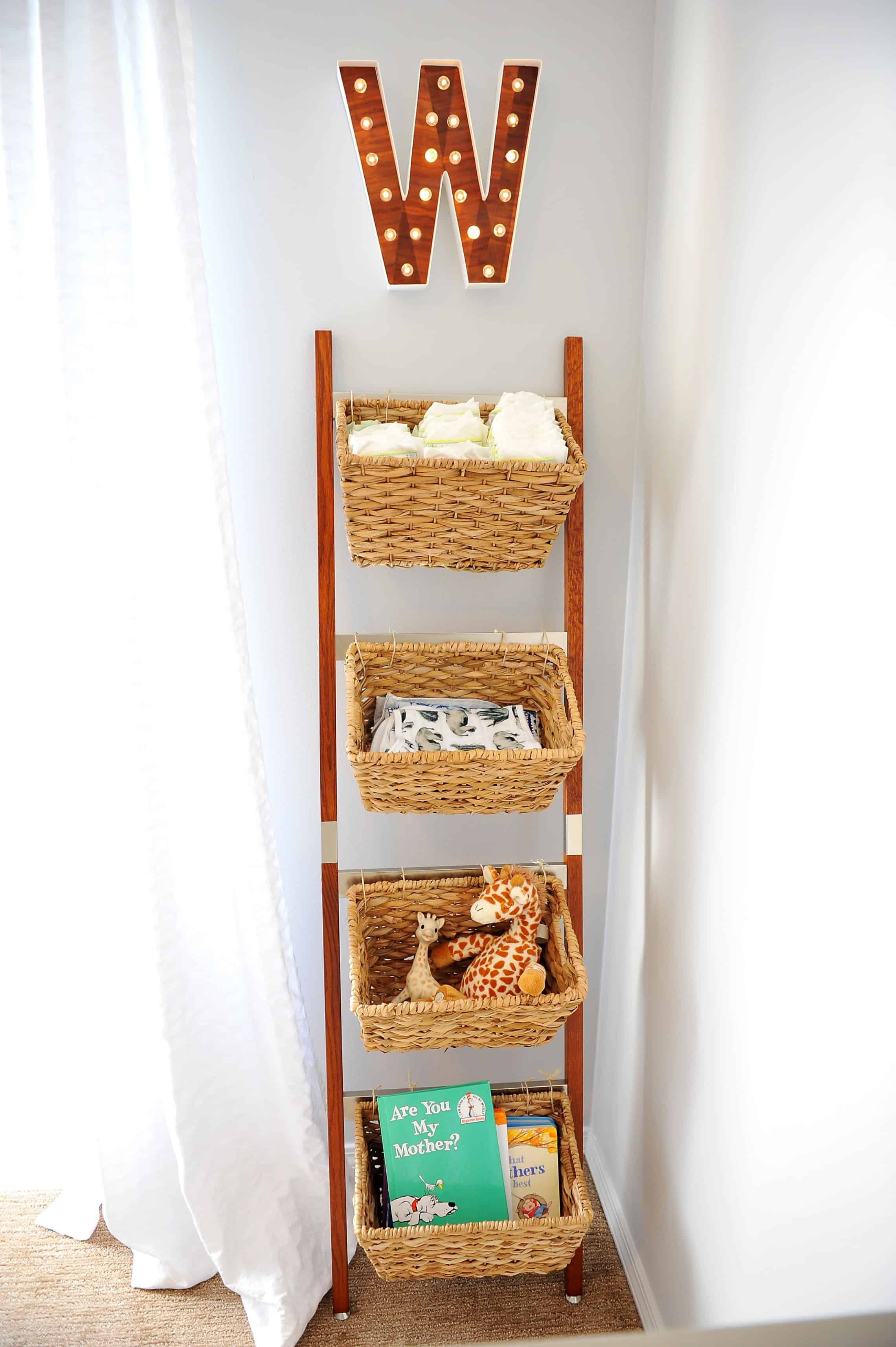 Wicker basket storage ladder with nursery items and hanging W over it