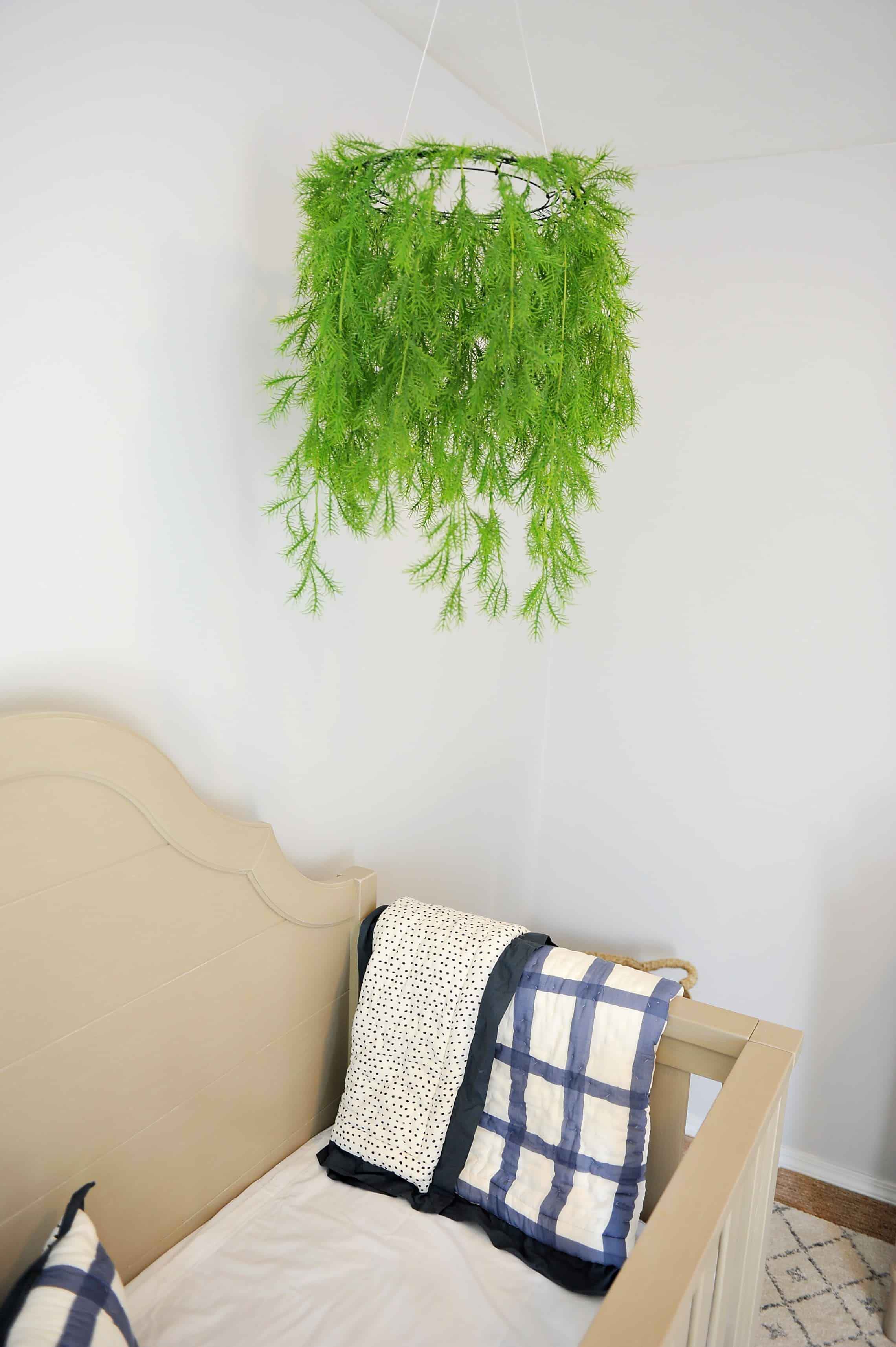Greenery mobile hanging over crib