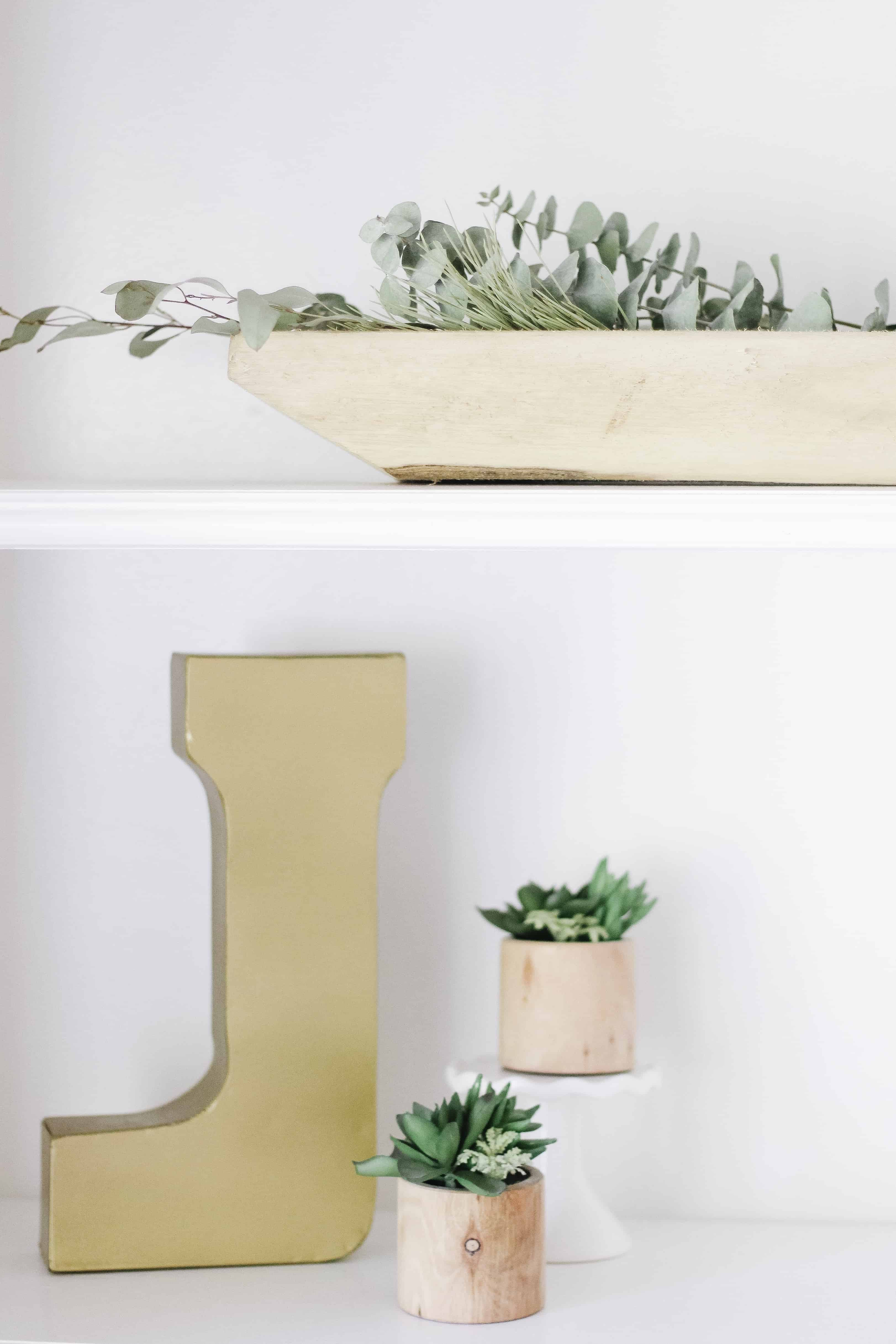 builtin shelving with gold J and wooden and greenery accents
