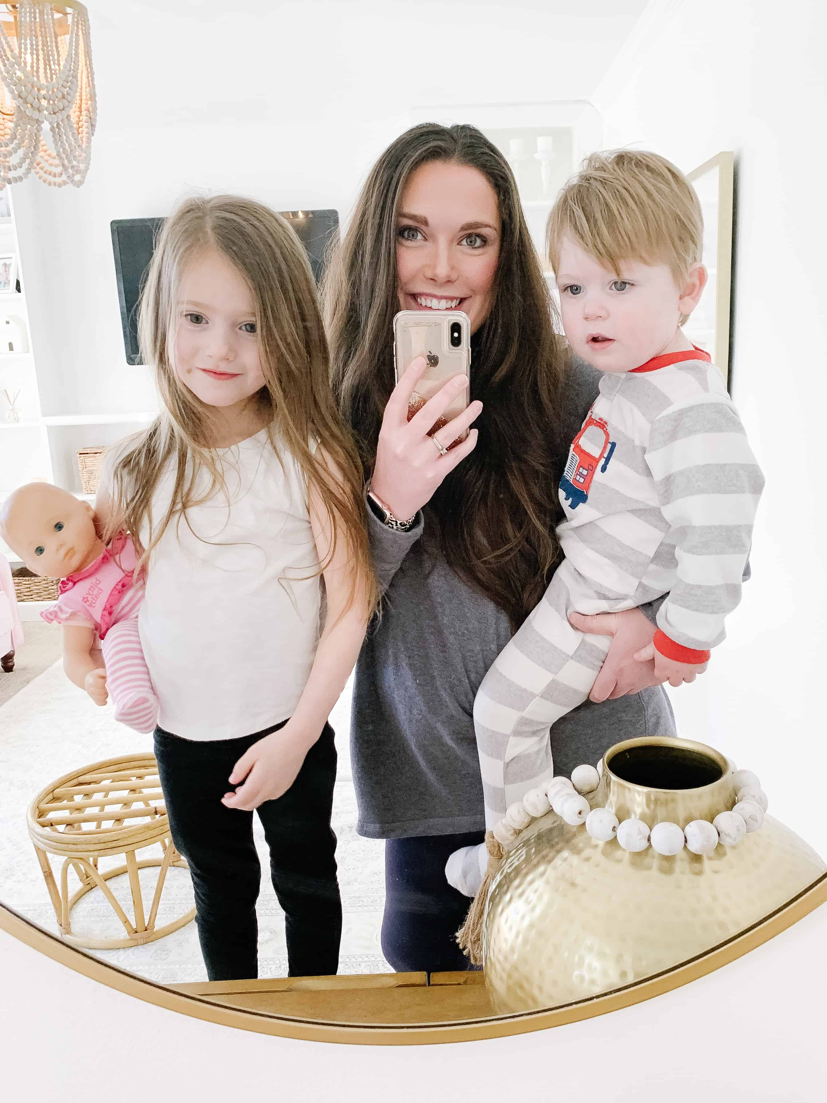 mom holding two toddlers looking in gold round mirror