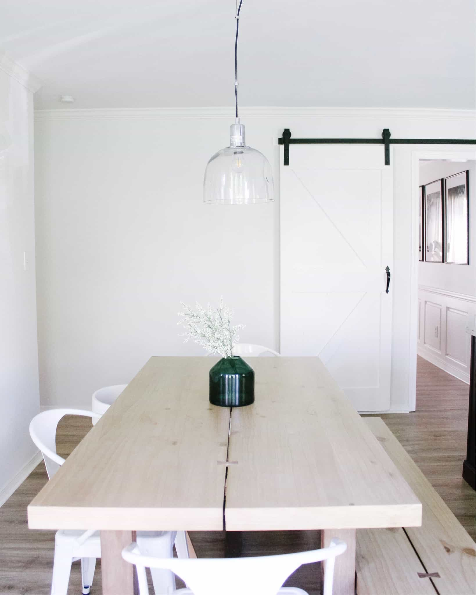 kitchen table with green vase on it and barn door