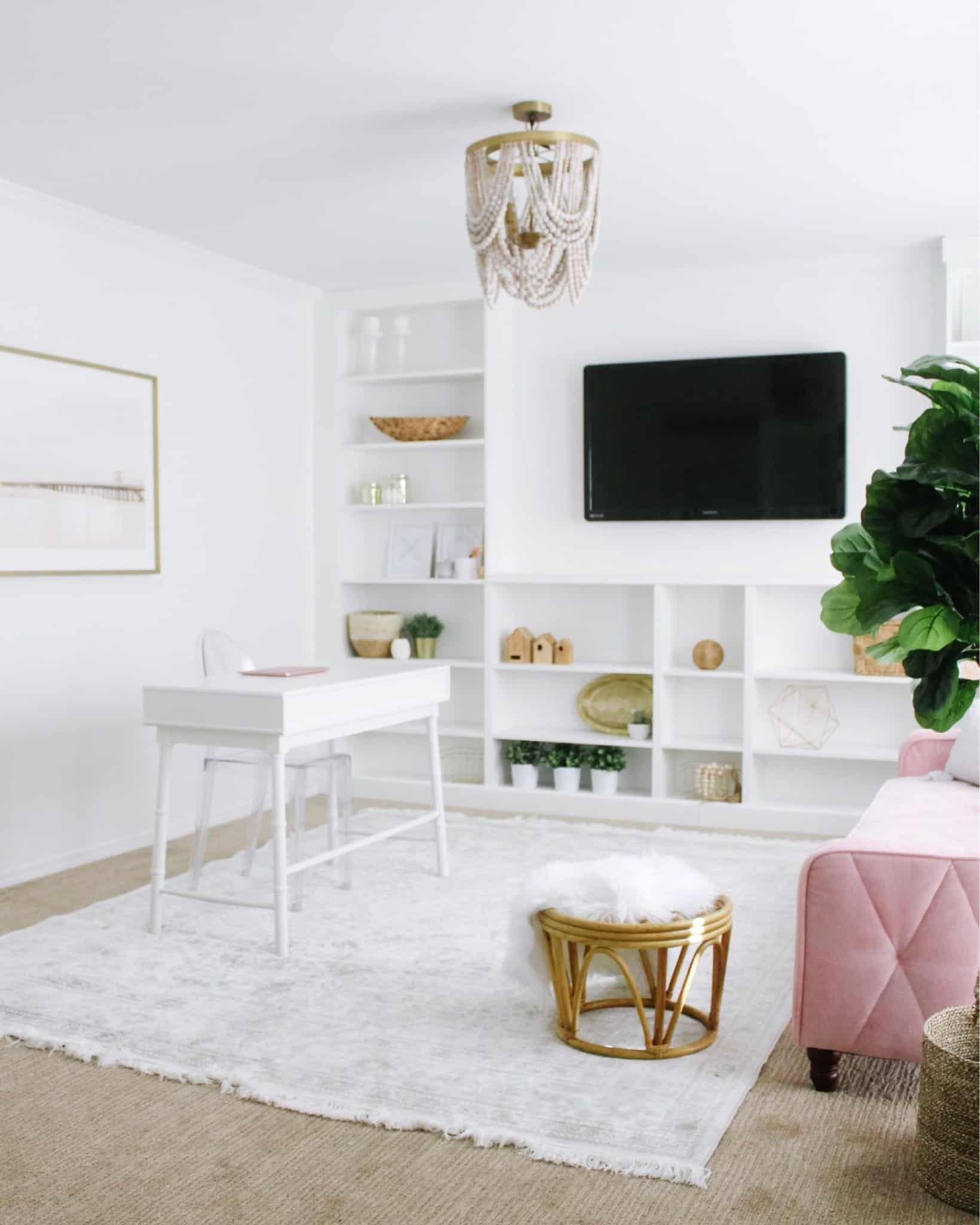 modern home office with wall of built ins and pink couch