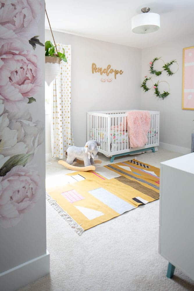 baby girl nursery with yellow rug