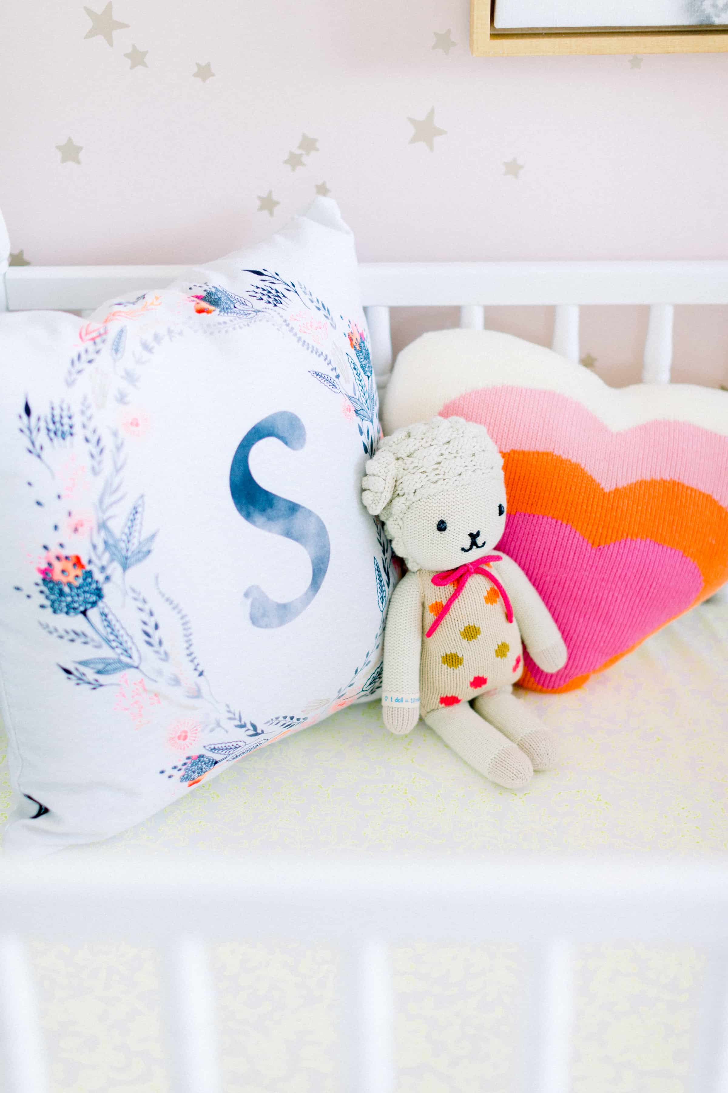 S pillow, cuddle and kind doll, and heart rainbow pillow in crib