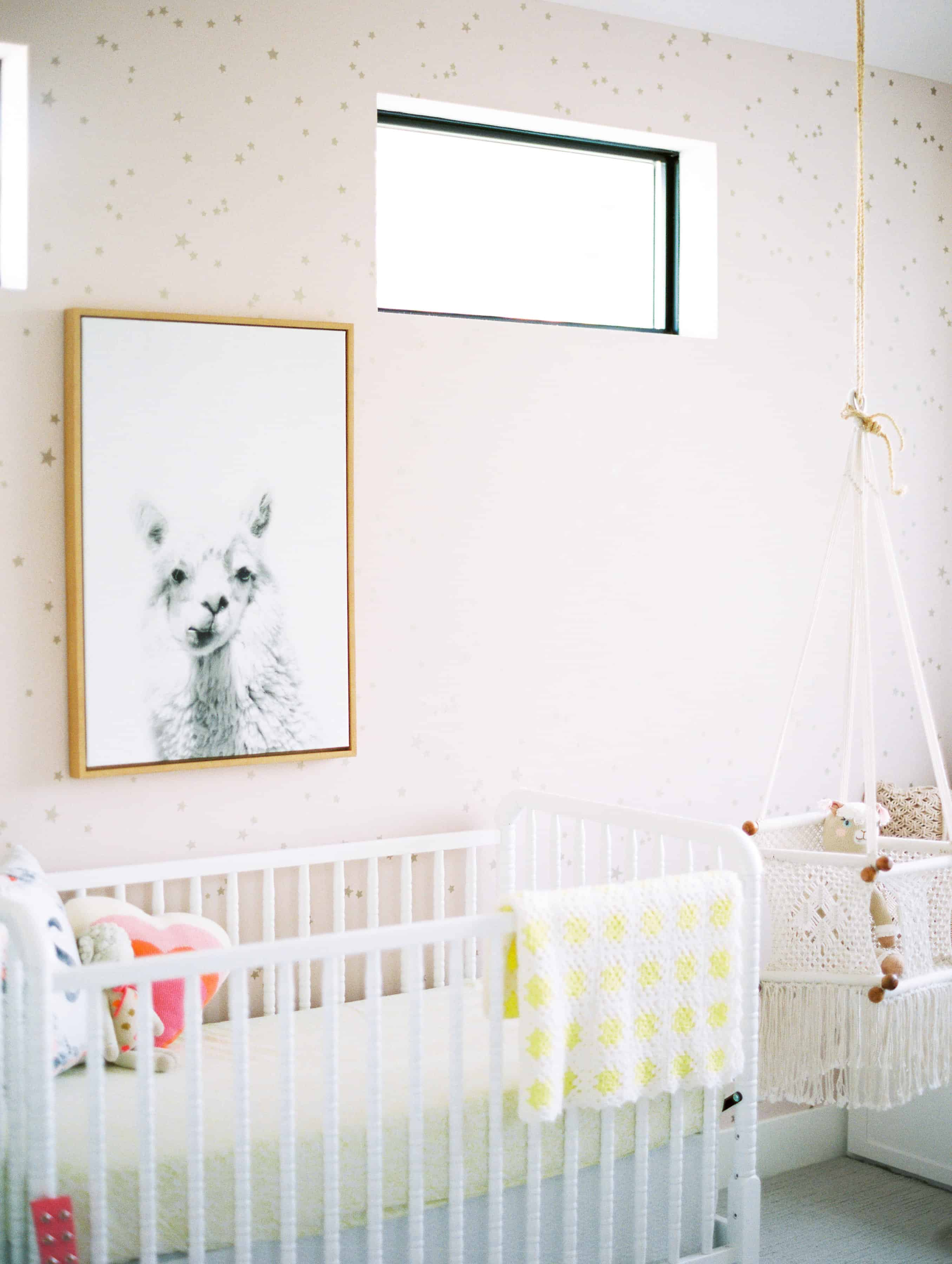 alpaca picture over white crib with pink walls