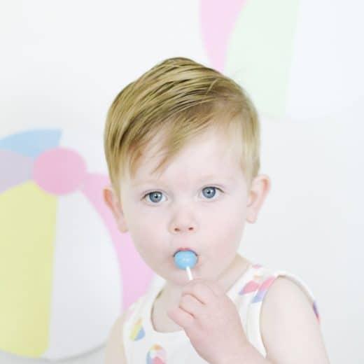 toddler boy in beach ball outfit eating sucker