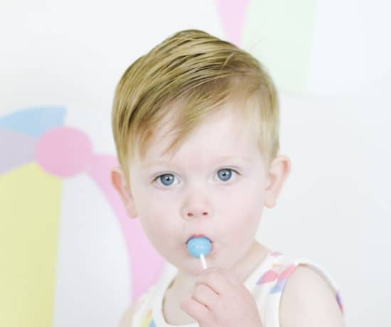toddler boy in beach ball outfit eating sucker