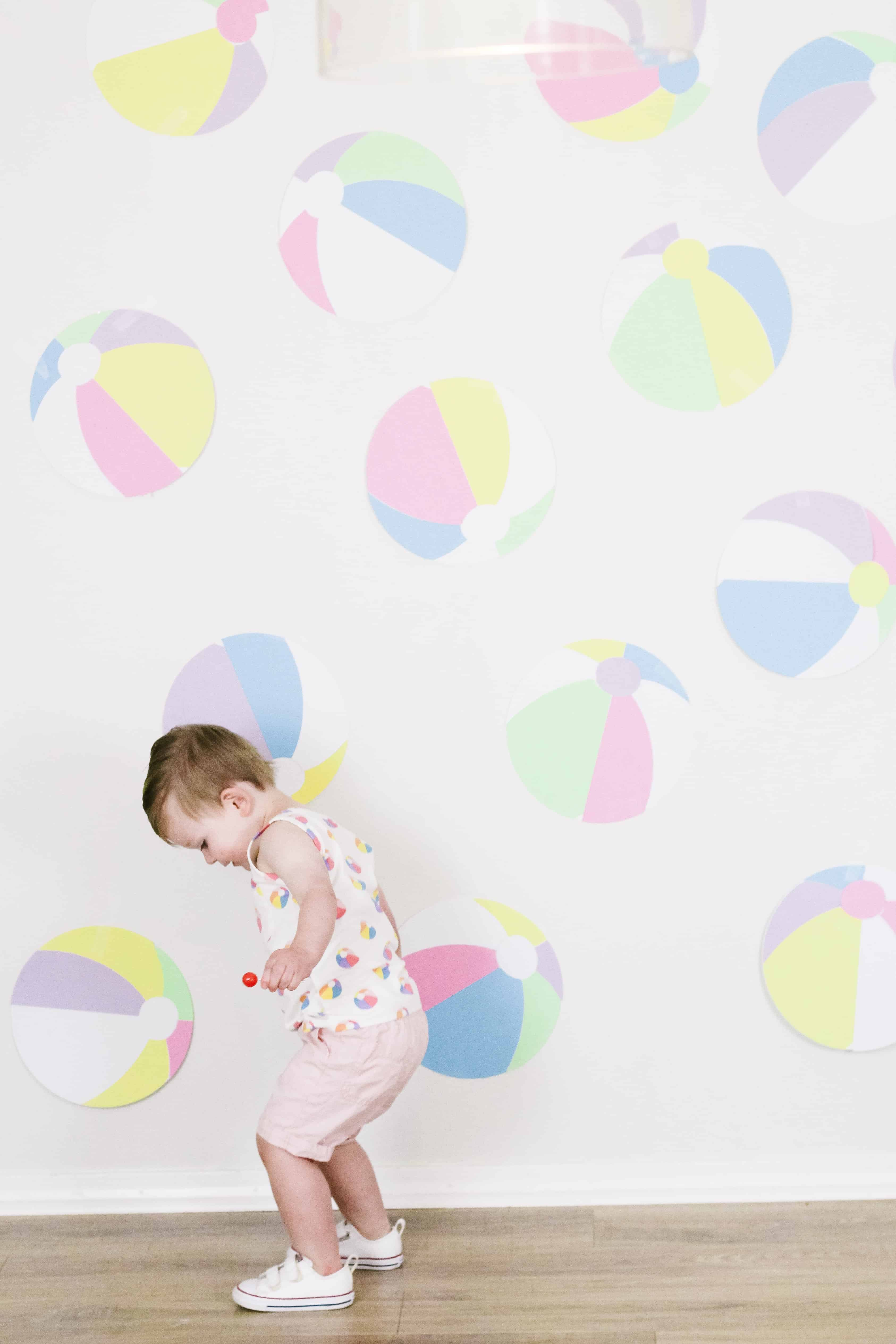 Toddler boy in beach ball themed outfit in front of beach ball wall