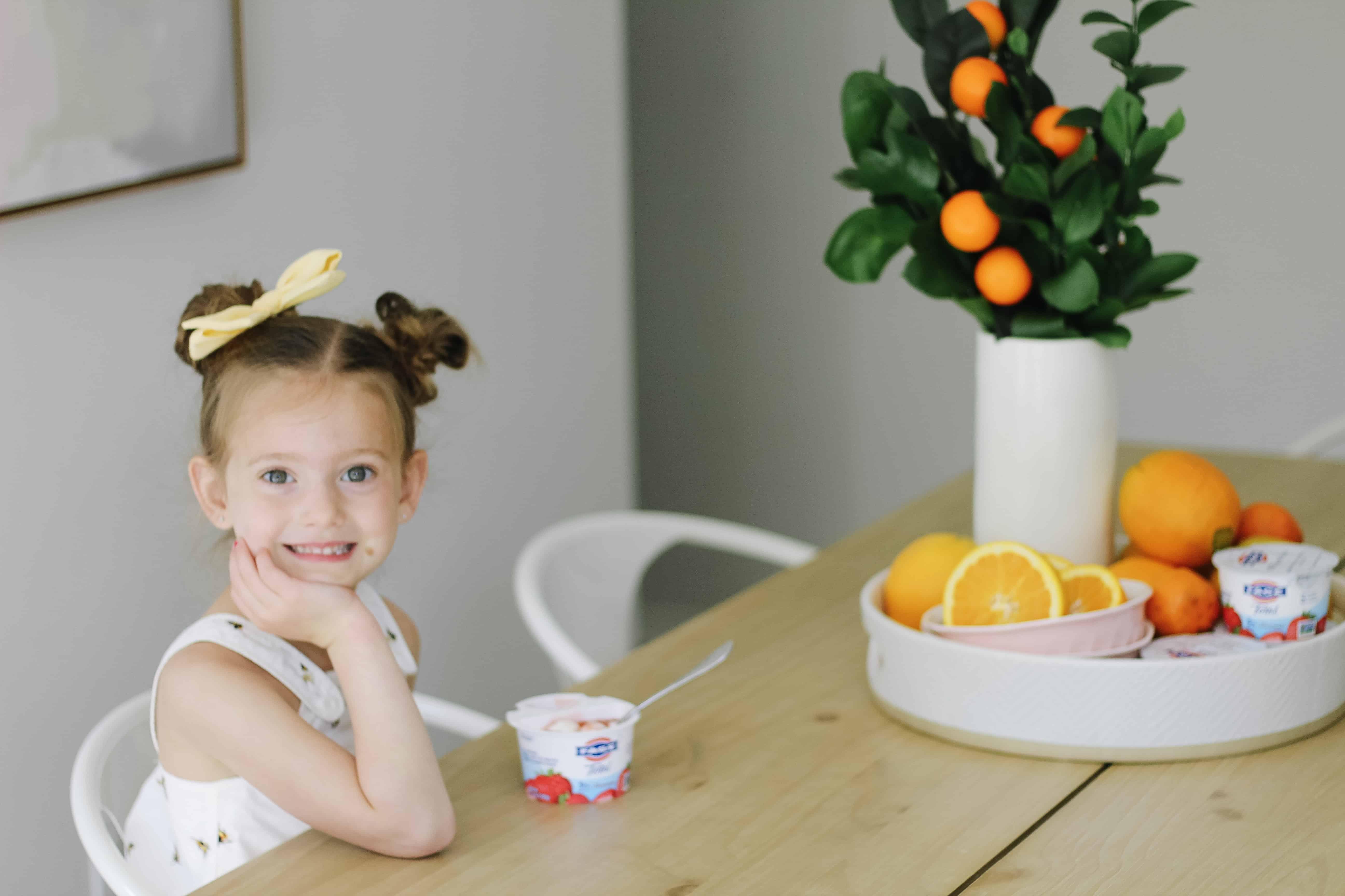 toddler girl at kitchen table eating