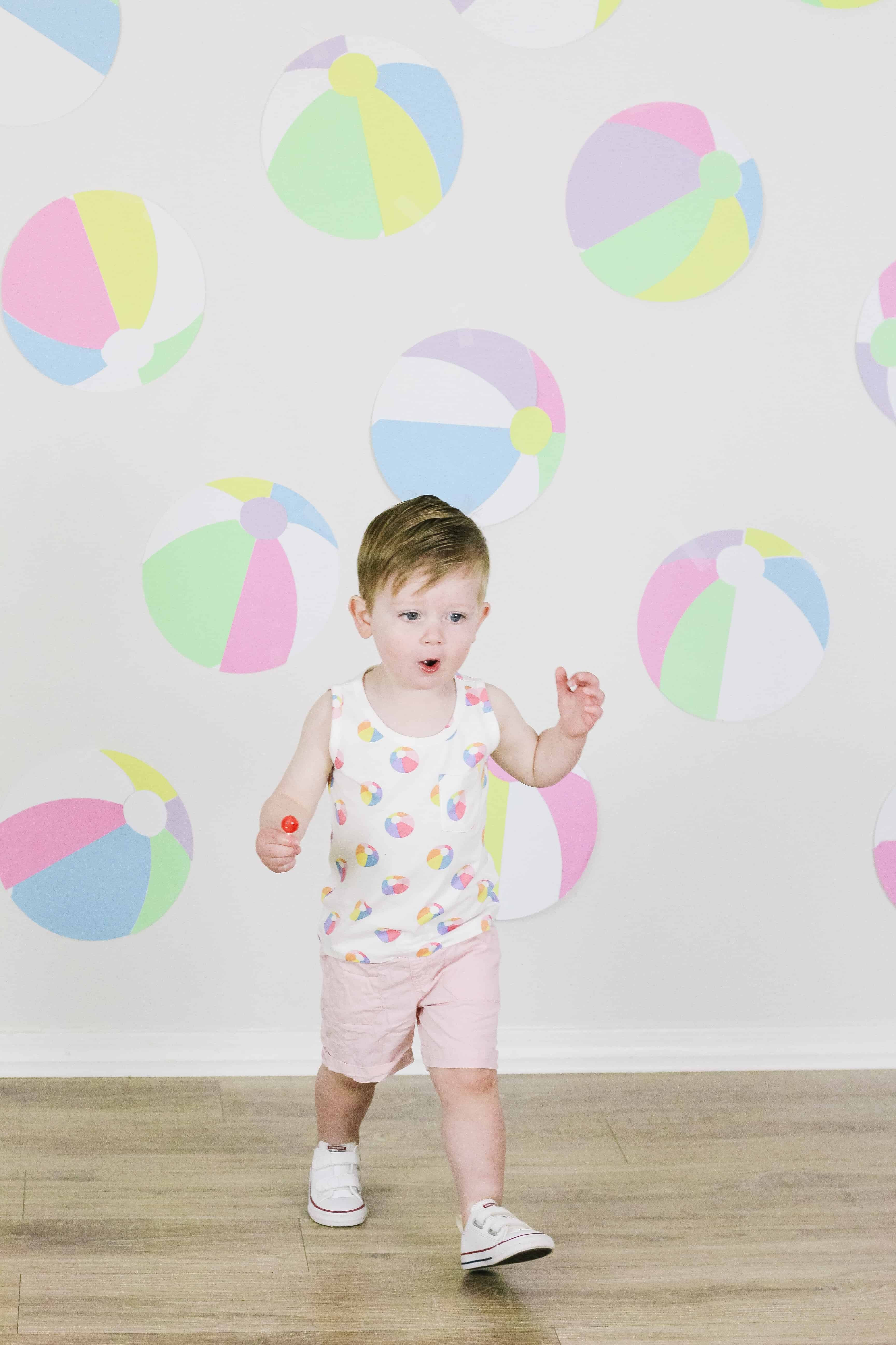Toddler in beach ball outfit in front of beach ball wall