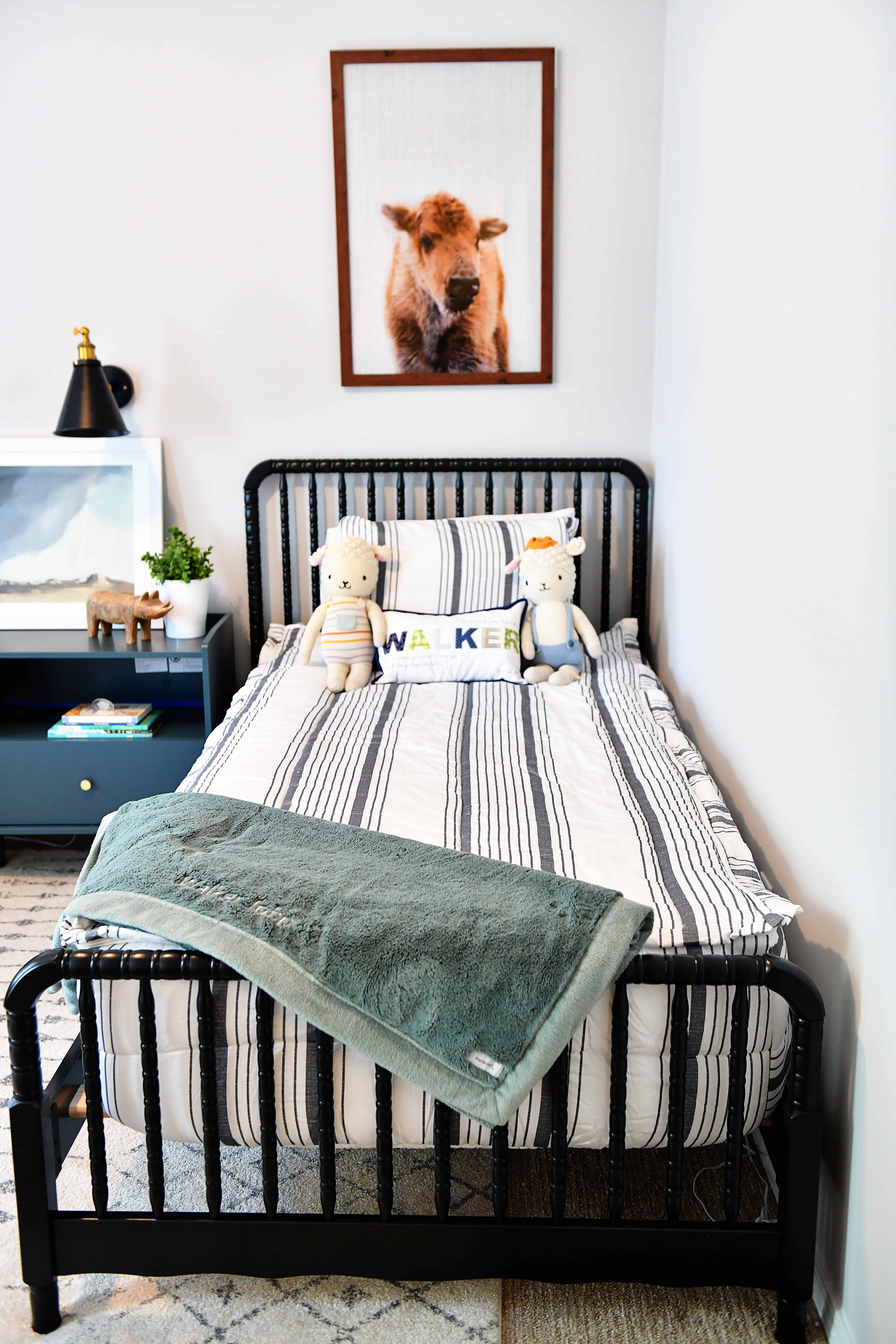 black twin Jenny Lind bed with baby buffalo print over it