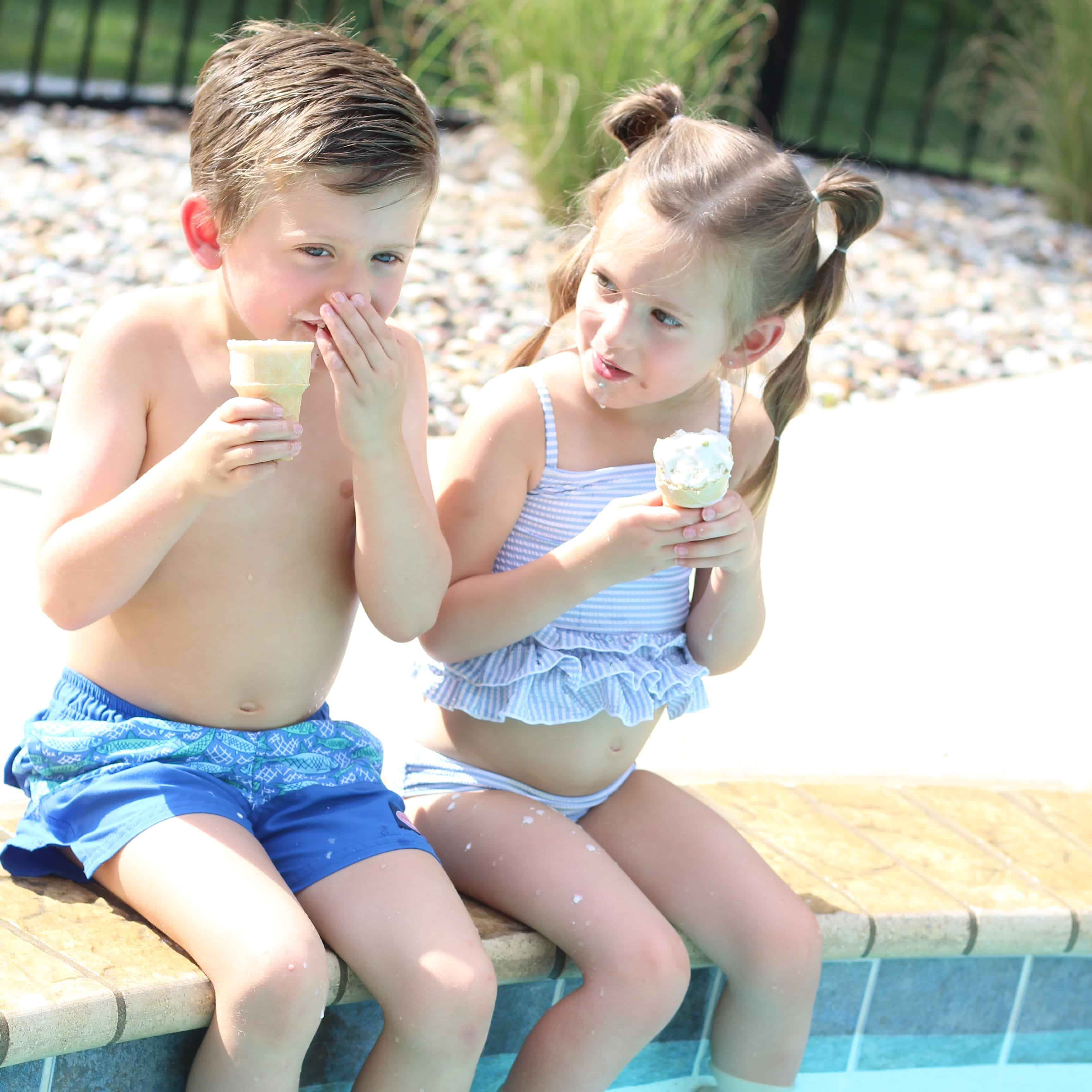 Two kids pool side eating ice-cream cones!