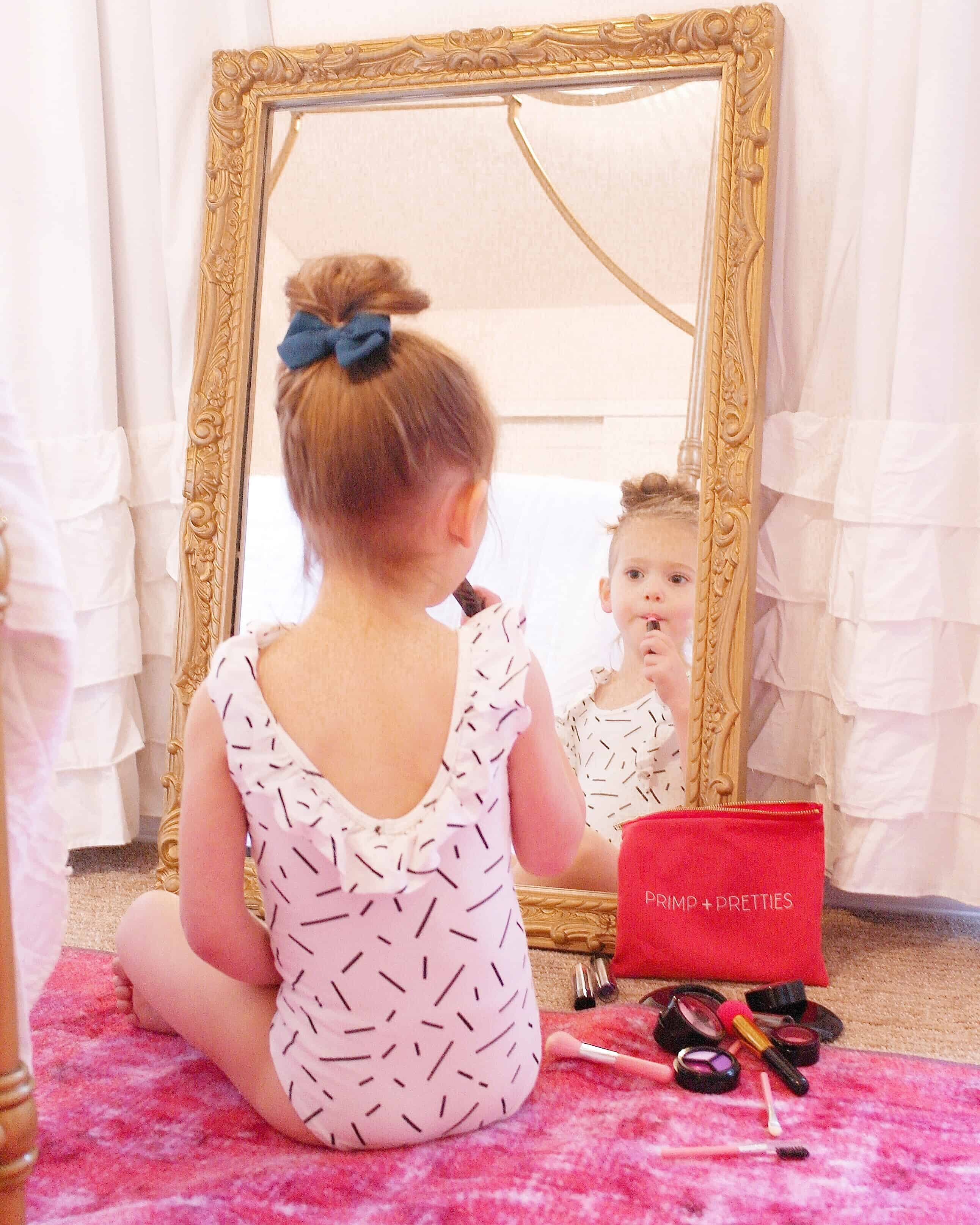 toddler girl putting on pretend makeup in gold mirror