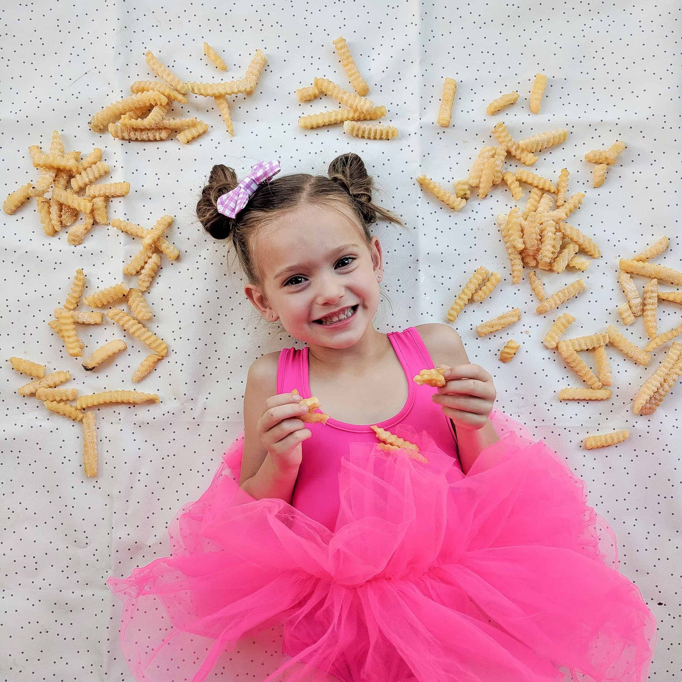 little girl in pink tutu surrounded by French fry