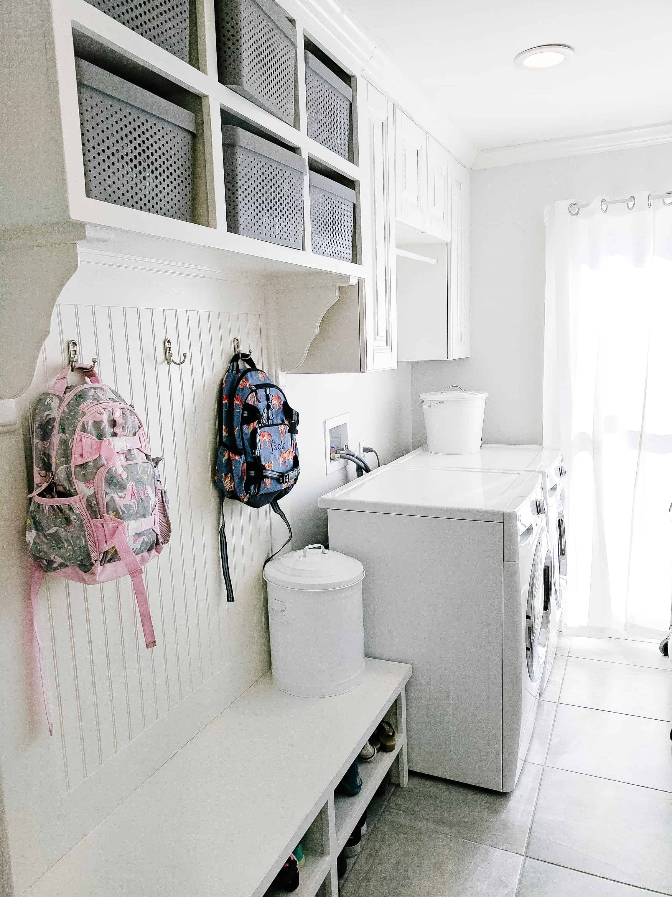 Laundry room with pottery barn kids backpacks hanging