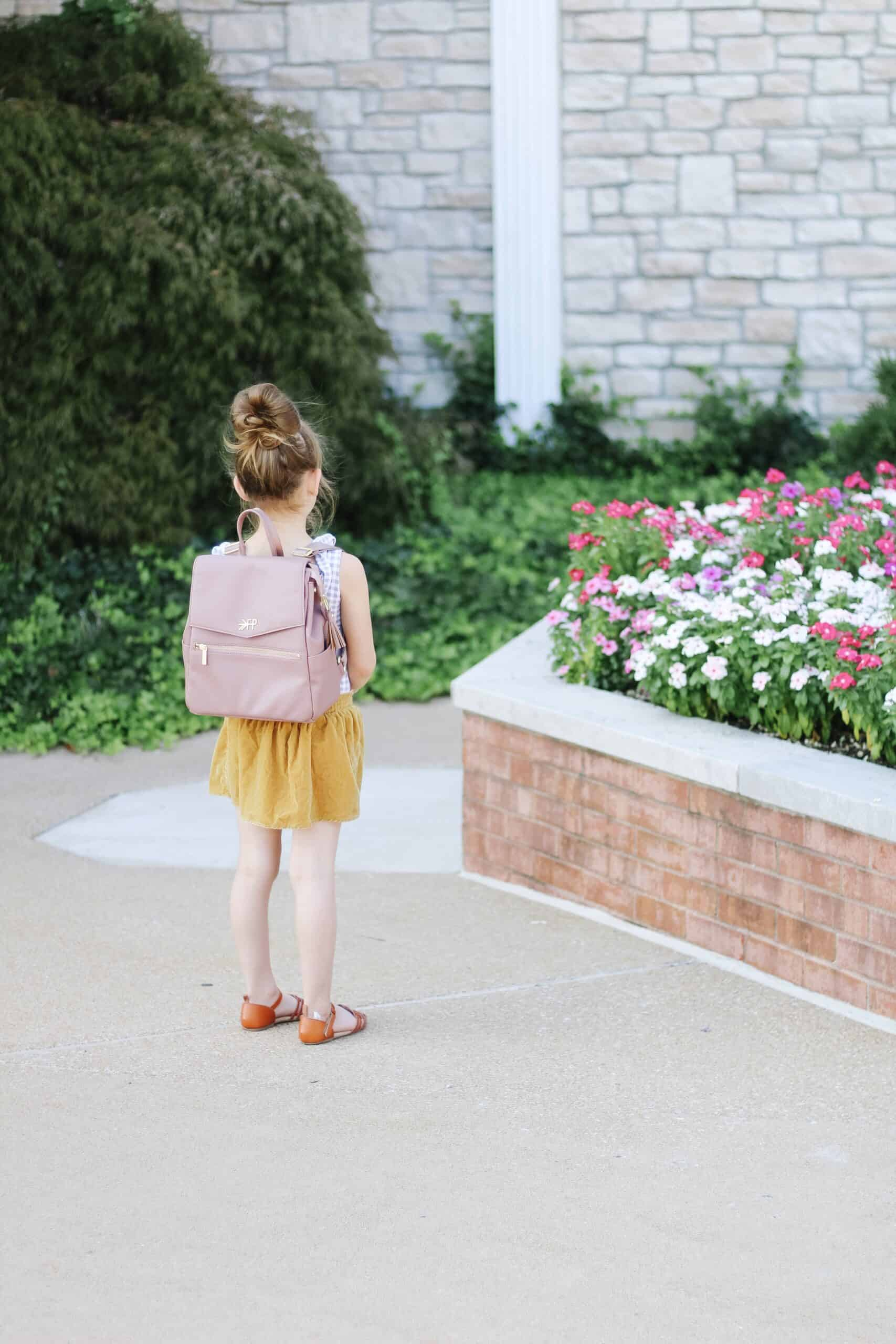 toddler girl wearing freshly picked mini diaper bag