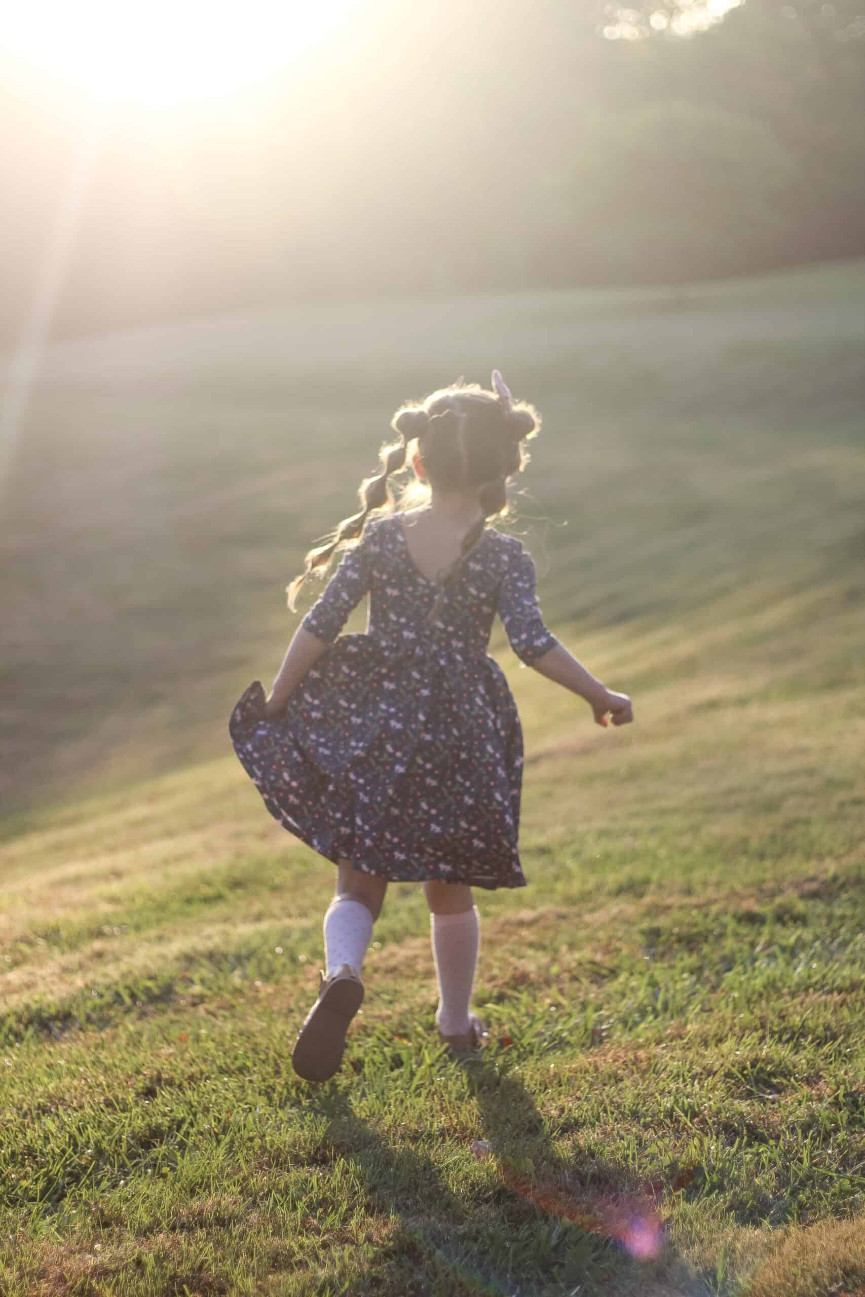 little girl running through a field during golden hour
