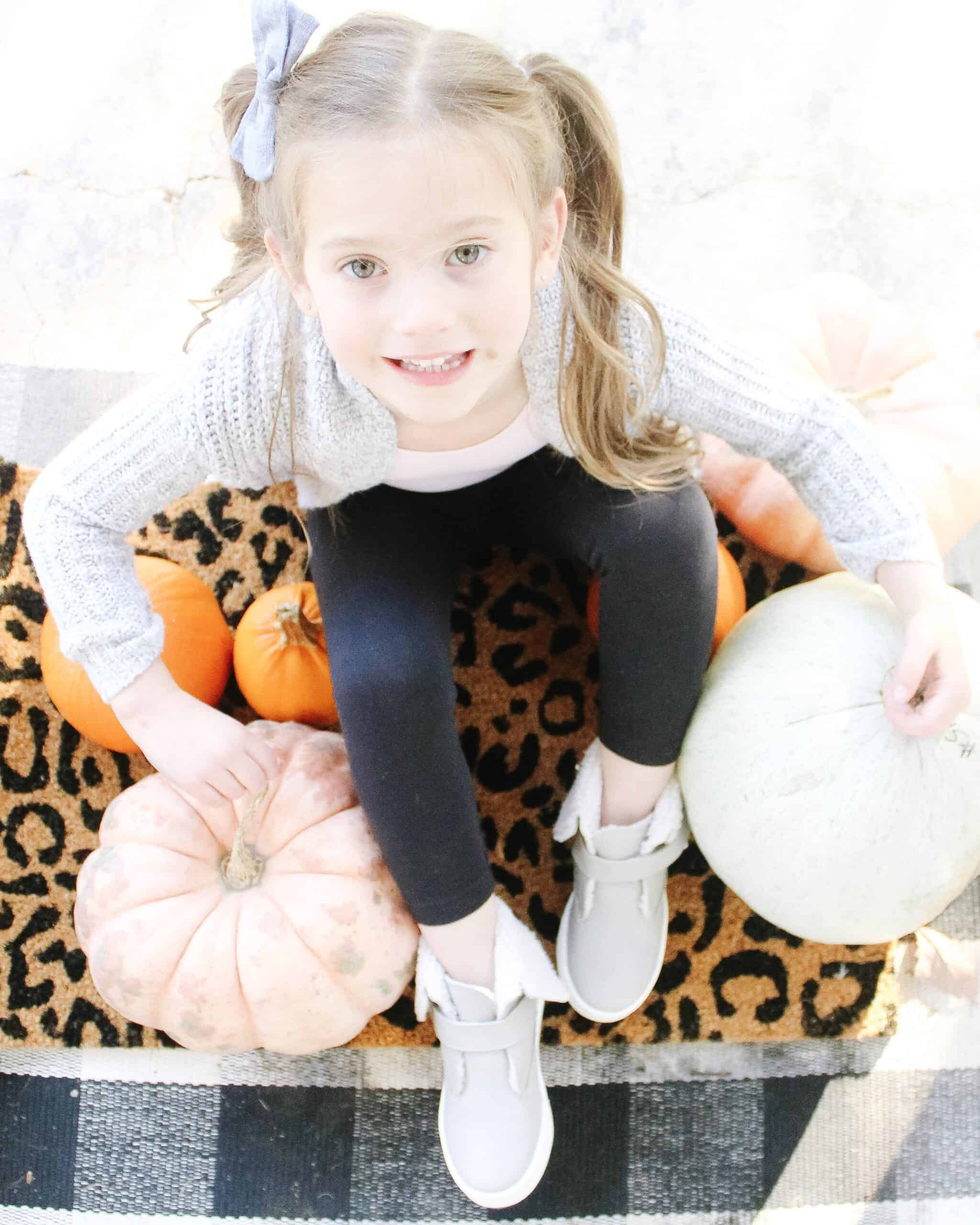 toddler girl in pumpkins