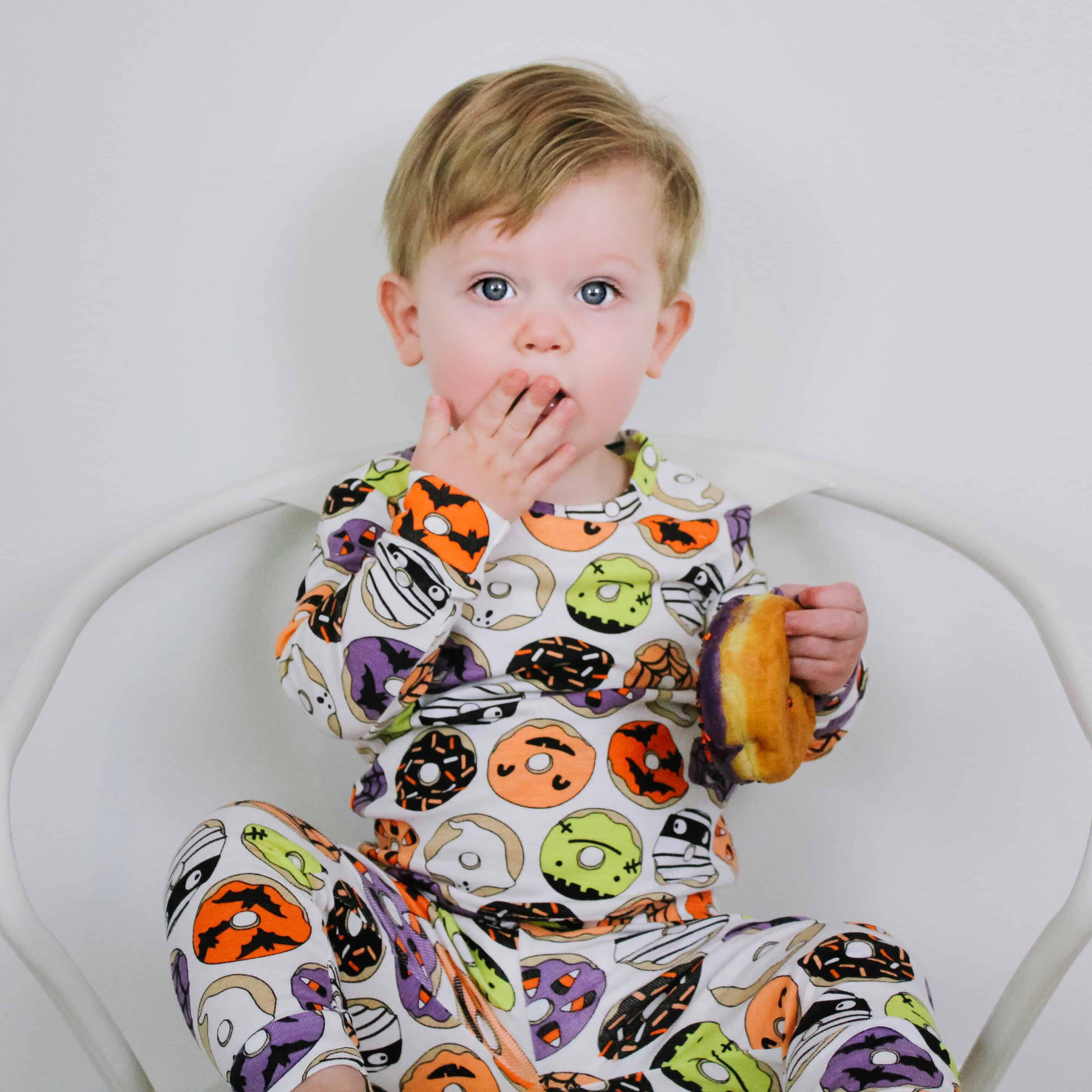 Little boy eating donut in donut halloween pajamas