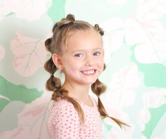 Little girl with bubble braid hair against green floral wall