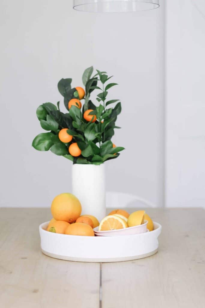 white platter with oranges and orange stems