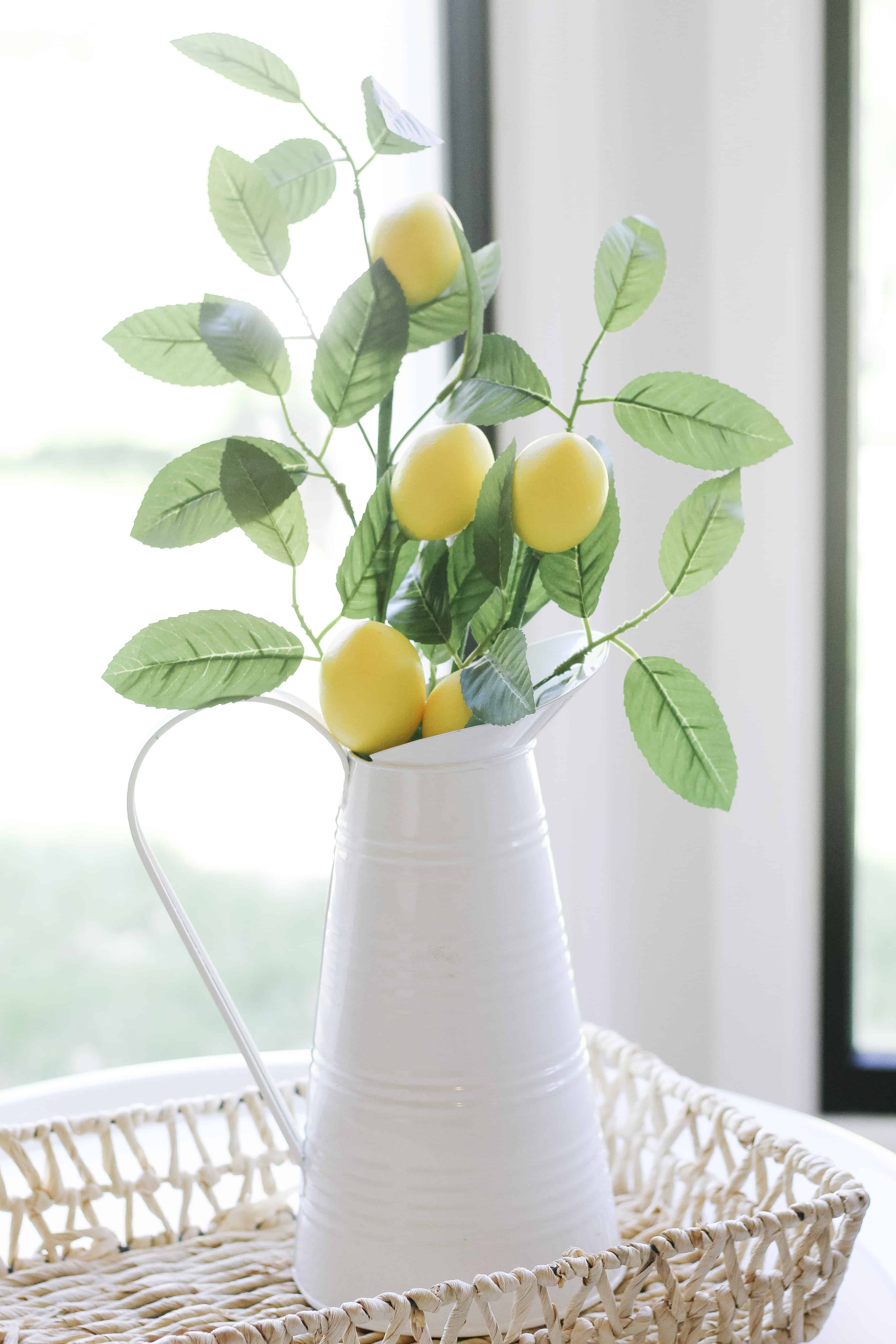 white metal pitcher with lemons and greenery inside