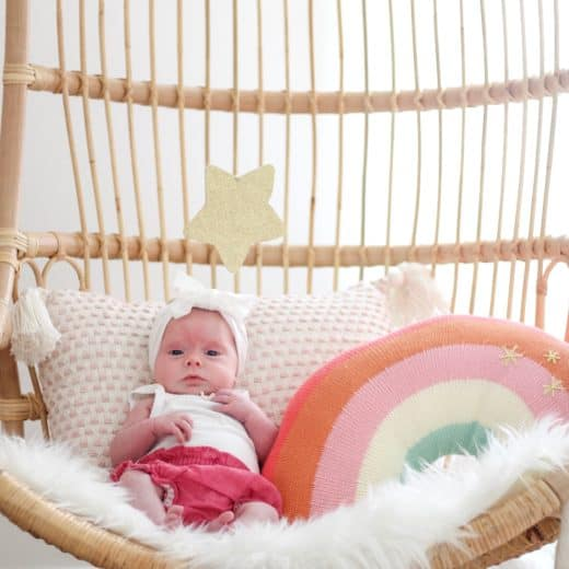 baby girl in Serena and lily hanging chair with rainbow pillow