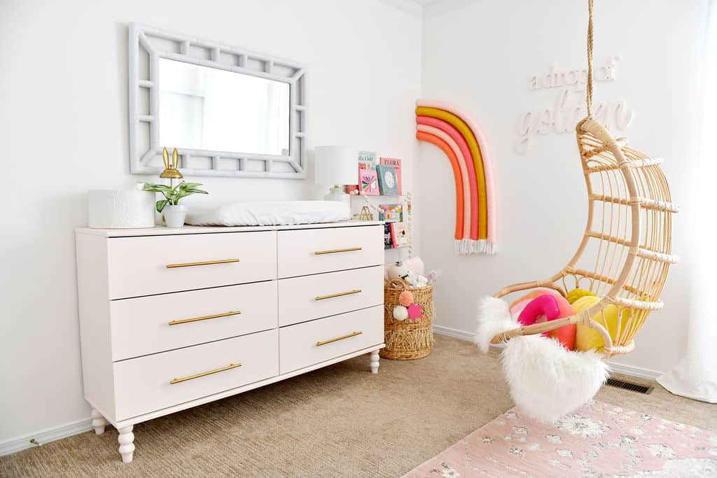 Nursery with rainbow on wall and pink Ikea dresser