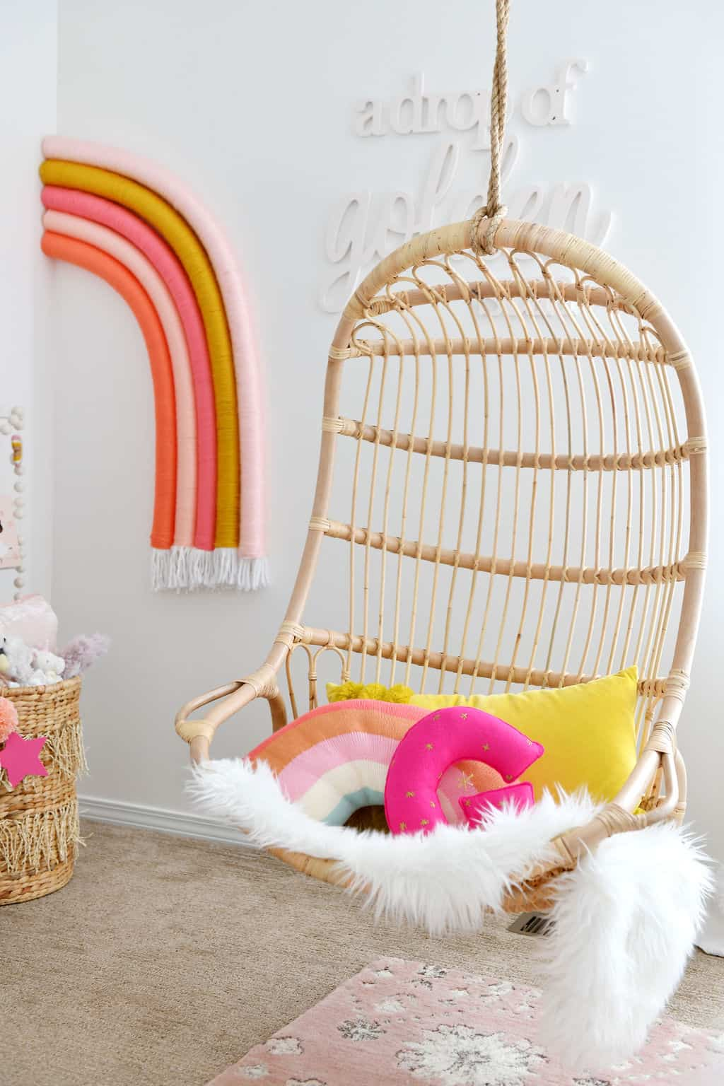 Serena and Lily rattan hanging chair with rainbow decor in Rainbow Nursery