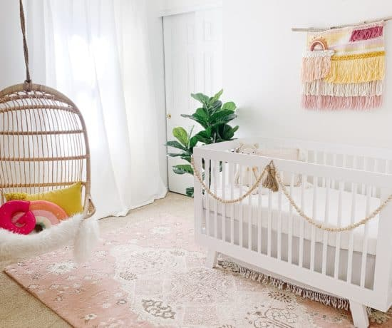 Nursery with pink rug and hanging Serena and lily chair