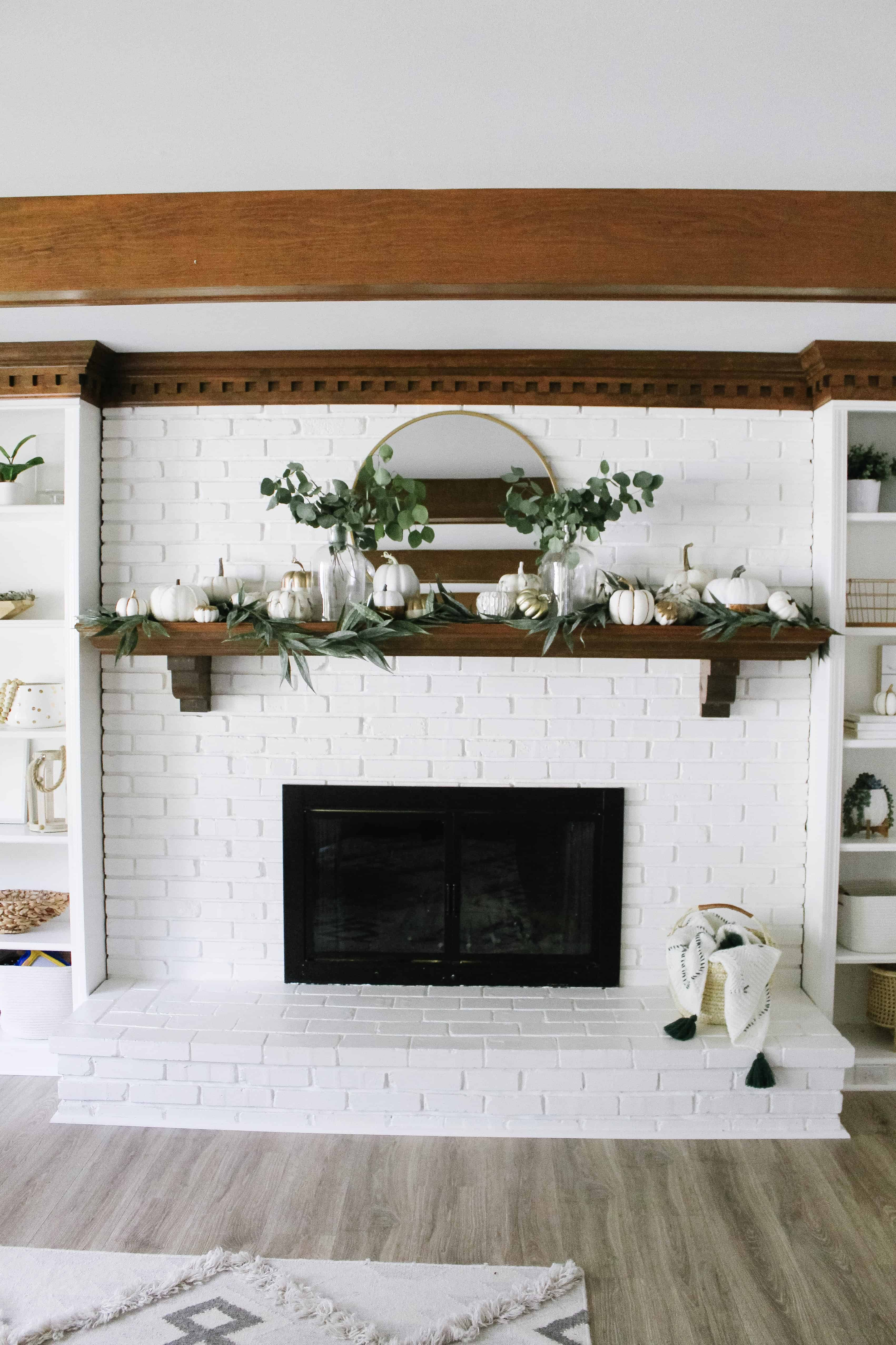 white brick mantle with neutral pumpkins