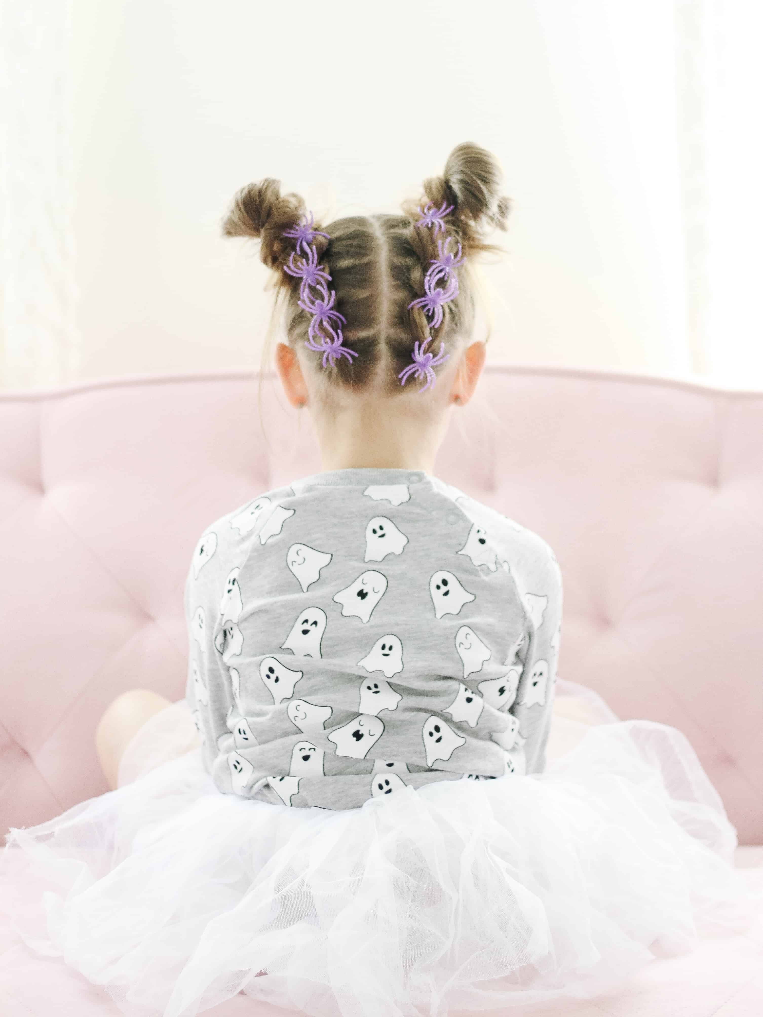 Toddler with spider rings in her hair for halloween hair